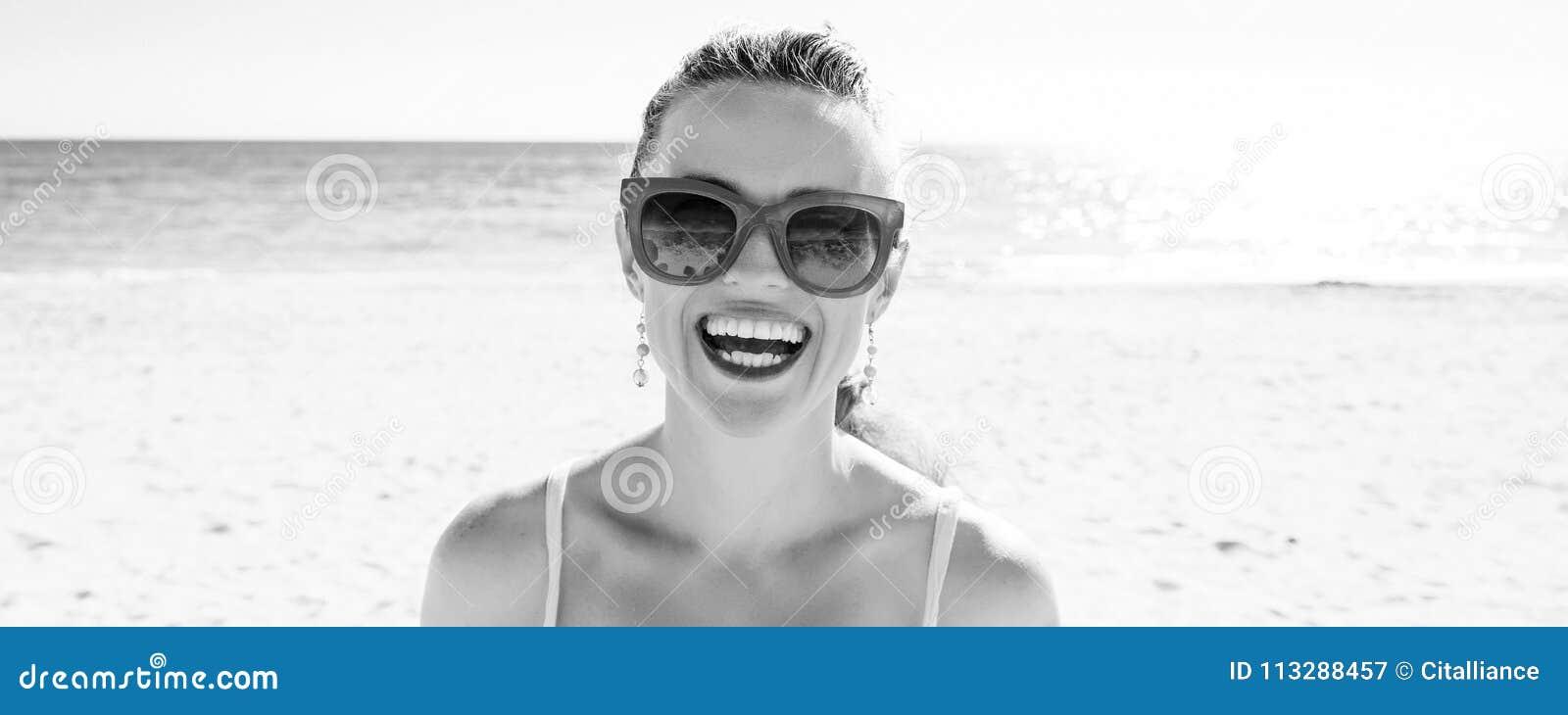 Усмехаясь молодая женщина на seashore
