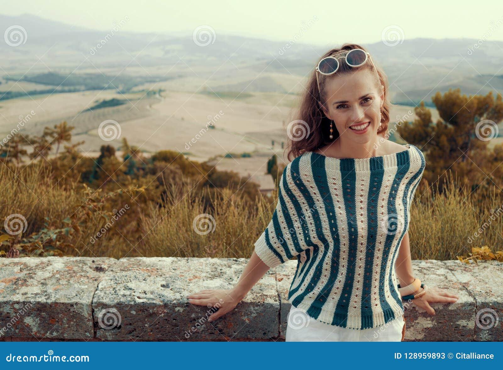 Усмехаясь молодая туристская женщина перед пейзажем Тосканы