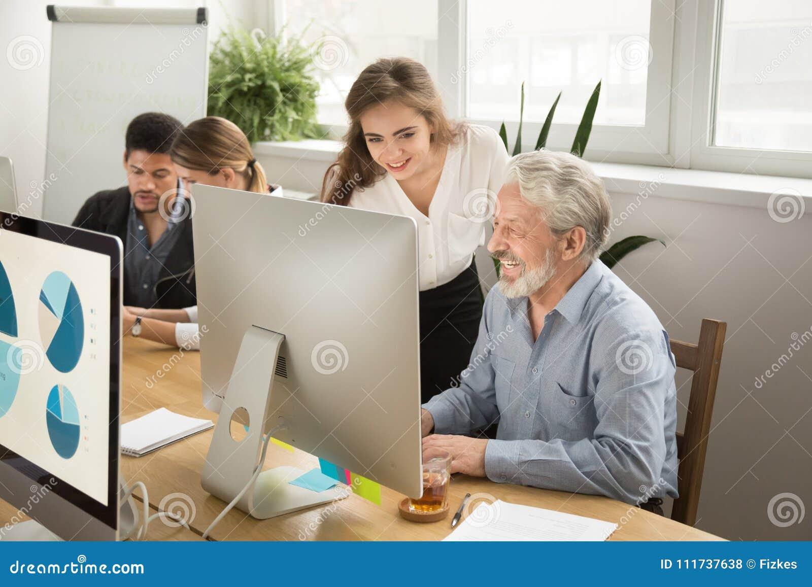 Усмехаясь молодой менеджер помогая старшему работнику с вычислительным бюро