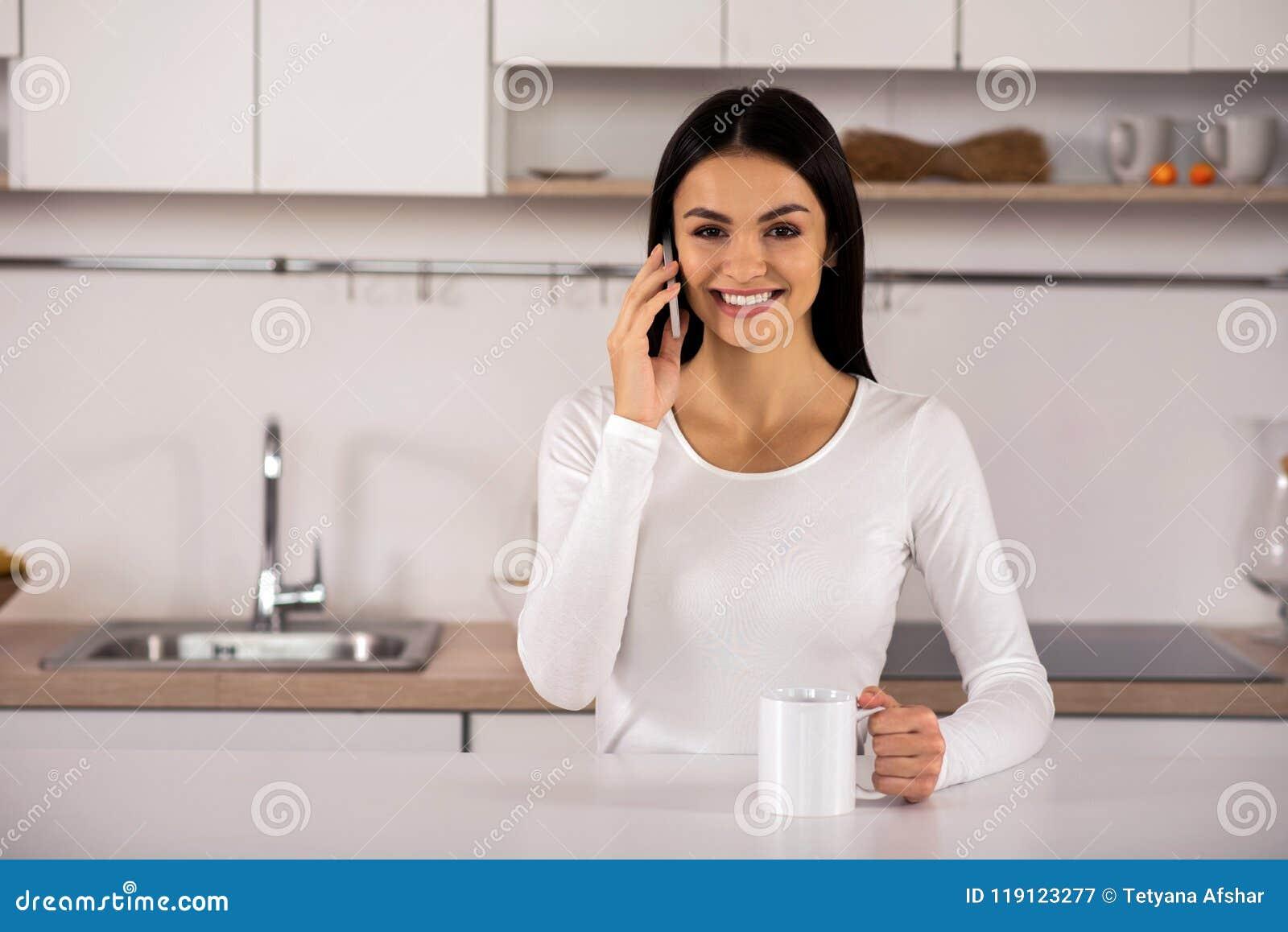 Усмехаясь молодые пары говоря на телефоне в кухне
