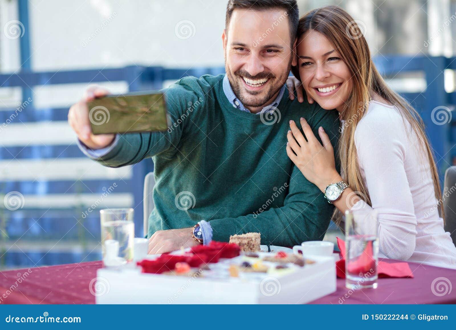 Усмехаясь молодые пары принимая selfie в на открытом воздухе кафе