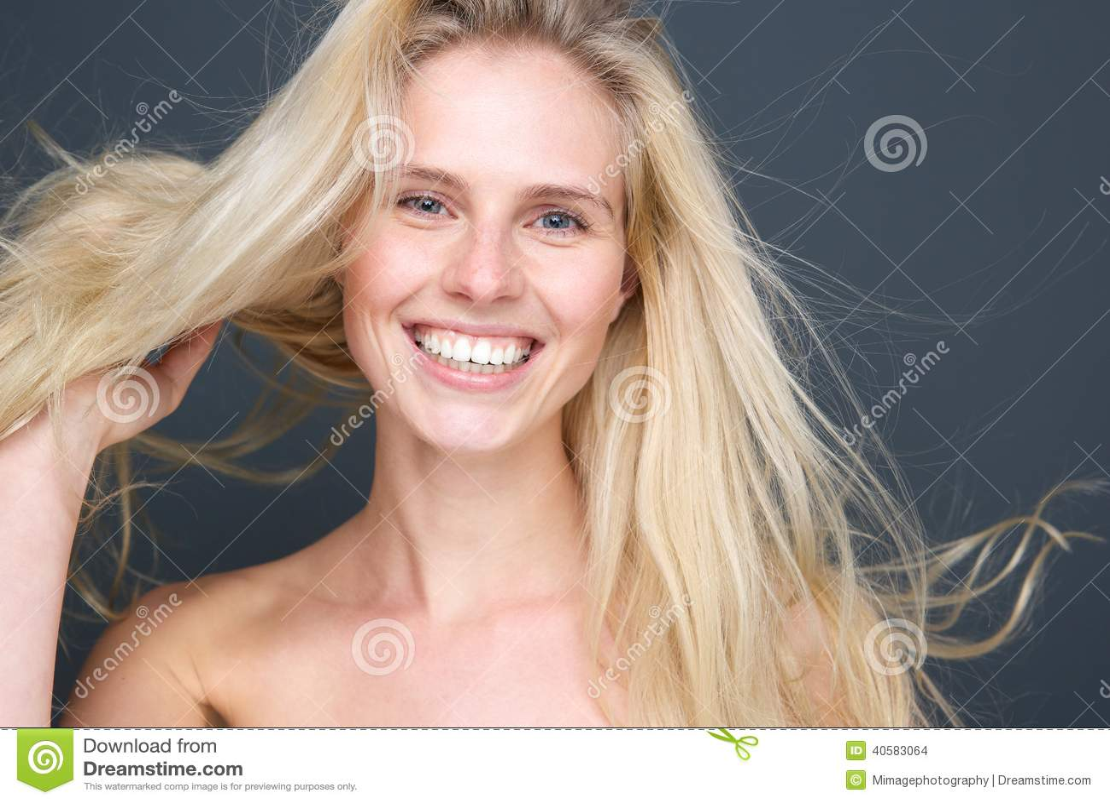 Усмехаясь молодая белокурая женщина с дуя волосами