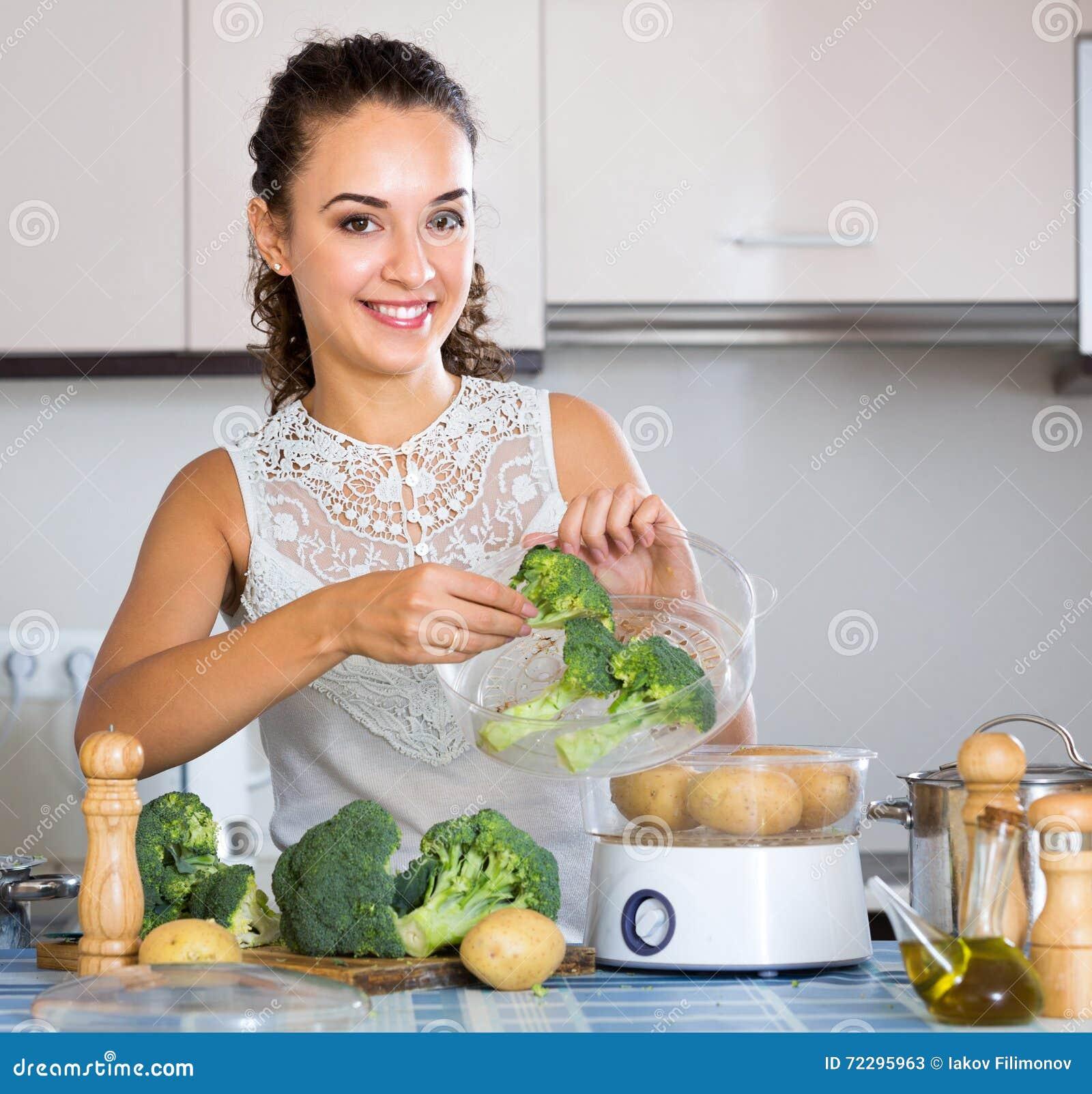 Download Усмехаясь молодая женщина варя брокколи Стоковое Изображение - изображение насчитывающей хобби, люди: 72295963