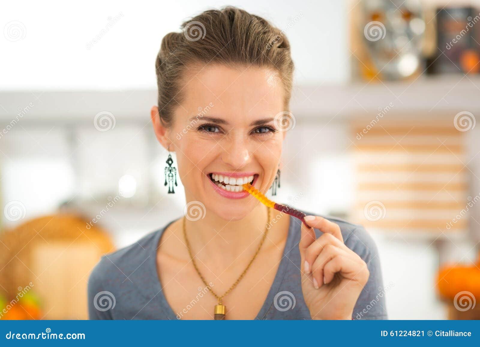 Усмехаясь молодая женщина есть конфету червя хеллоуина камедеобразную