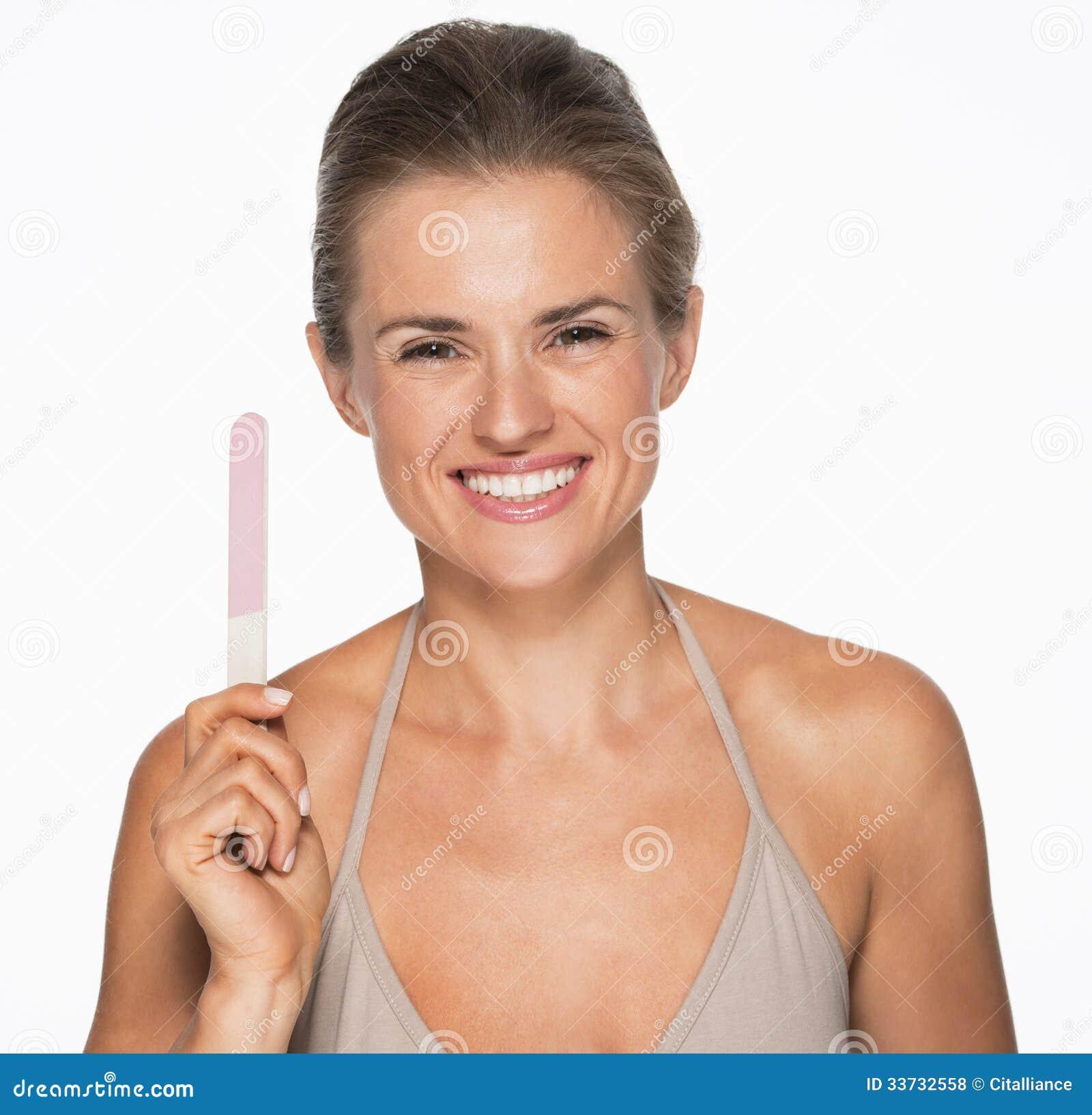Усмехаясь молодая женщина показывая пилочку для ногтей