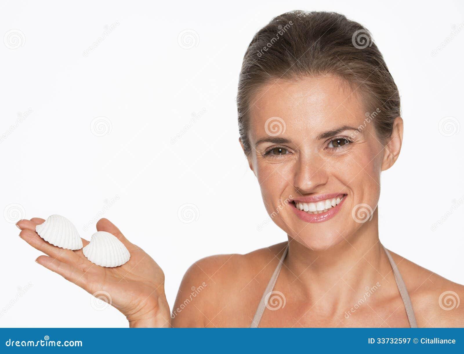 Усмехаясь молодая женщина показывая seashells
