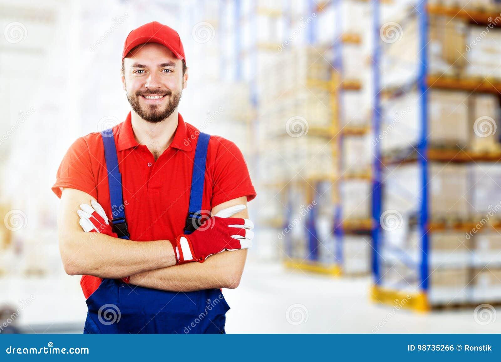 усмехаясь молодой работник склада в красной форме