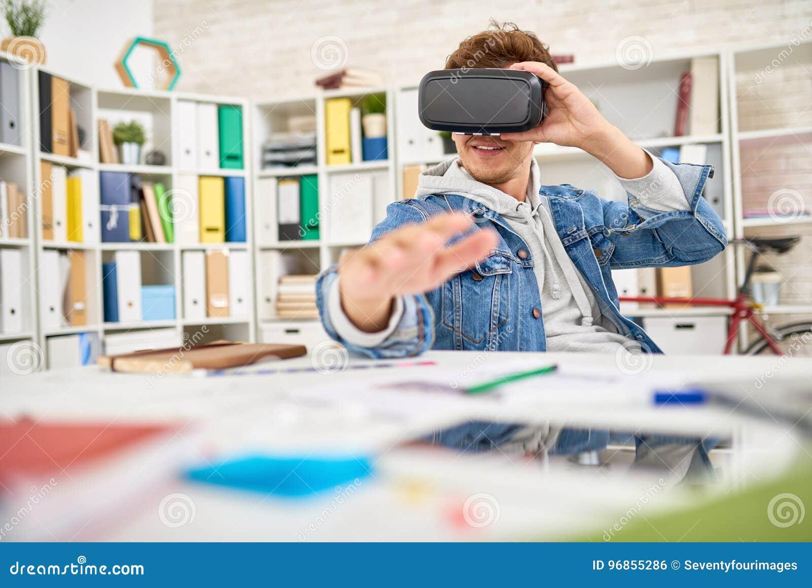 Усмехаясь молодой человек используя стекла VR на работе