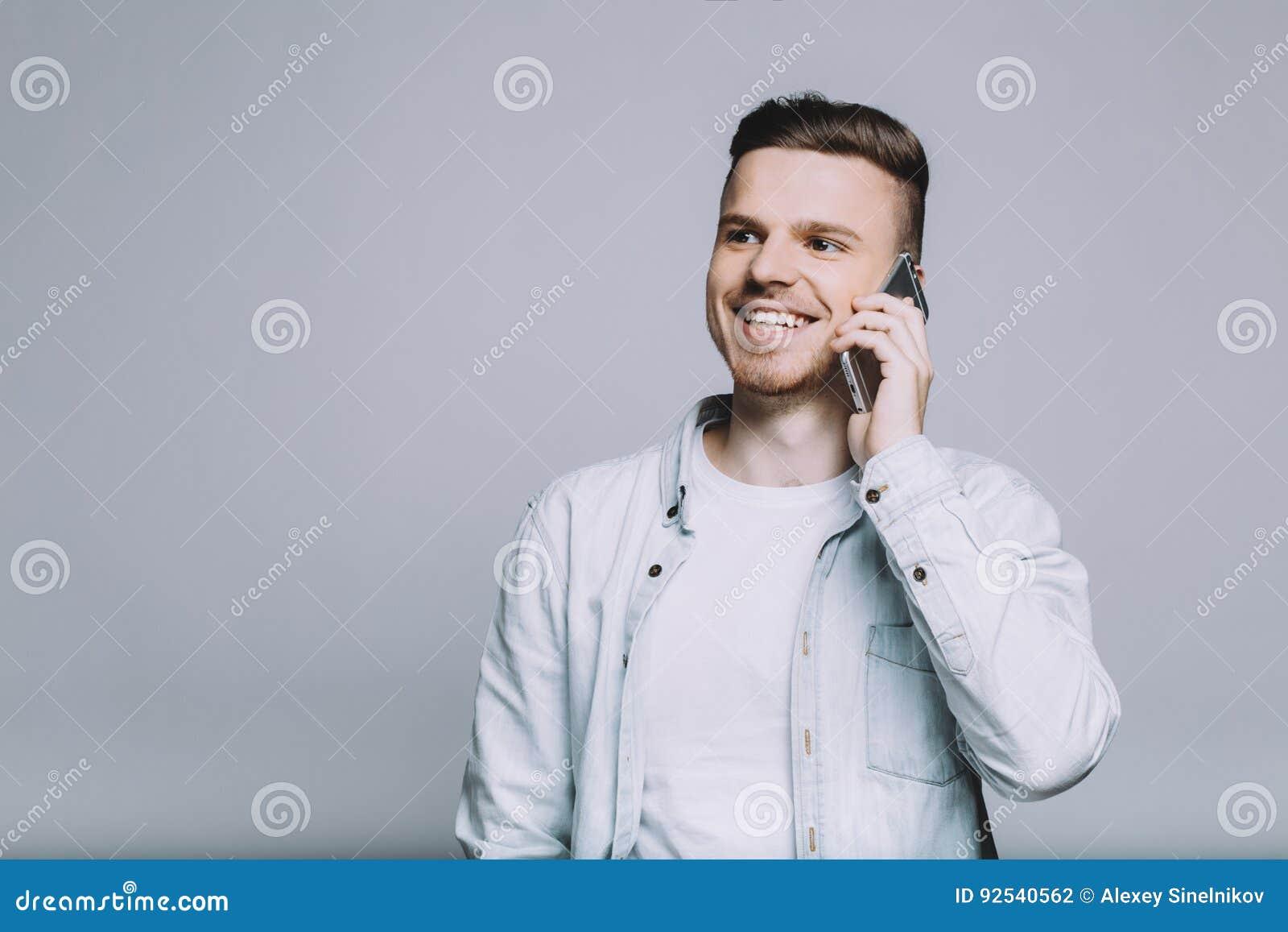 Усмехаясь молодой человек с бородой в белой рубашке