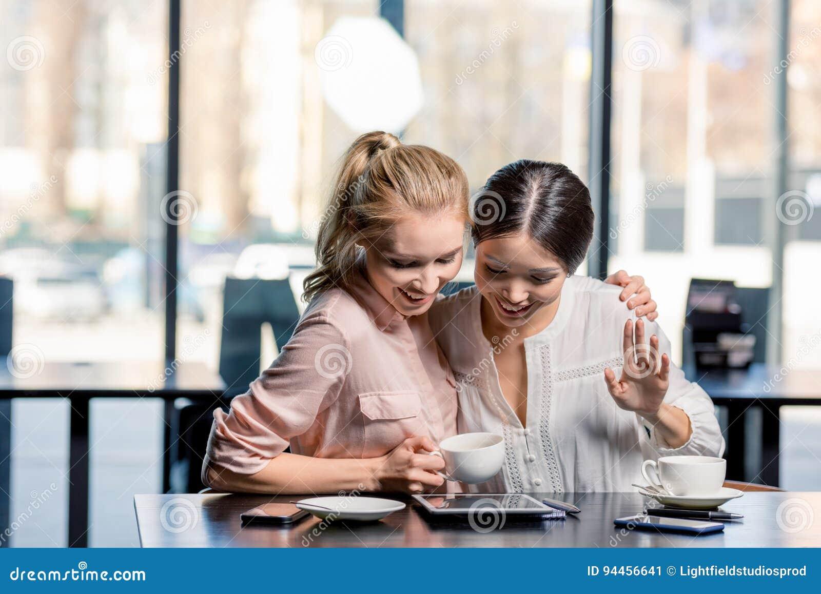 Усмехаясь молодые женщины используя цифровую таблетку пока выпивающ кофе в кафе