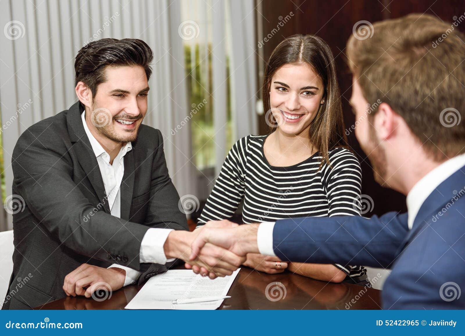 Усмехаясь молодые пары тряся руки с страховым инспектором