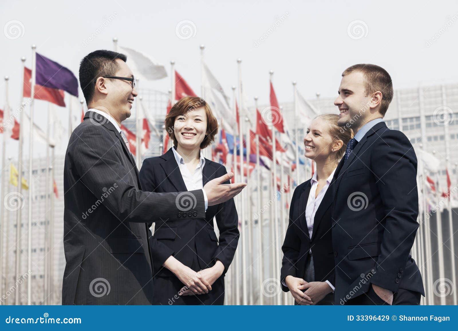 4 усмехаясь мульти-этнических бизнесмены говоря outdoors в Пекине, фарфоре
