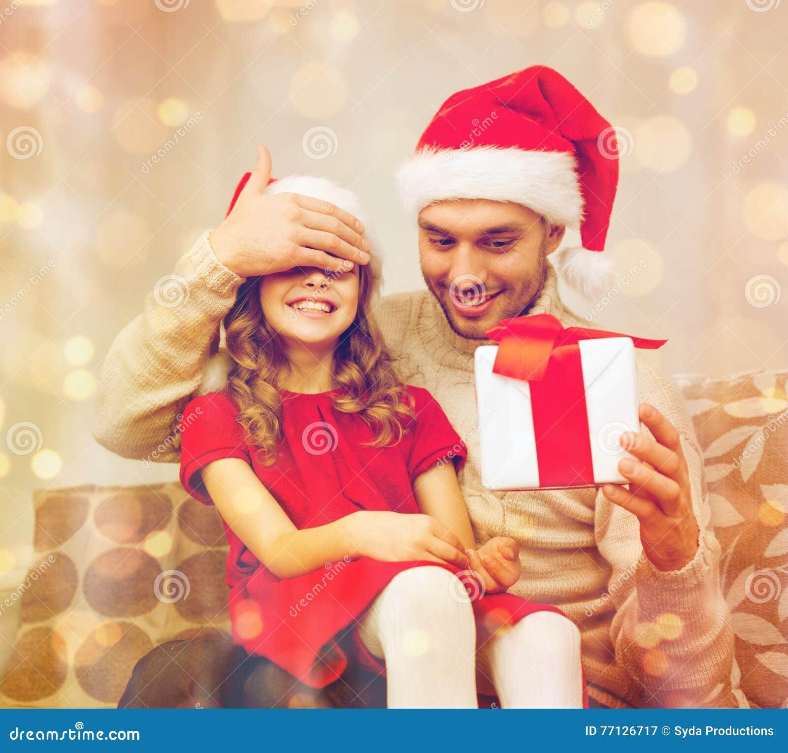 Усмехаясь отец удивляет дочь с подарочной коробкой