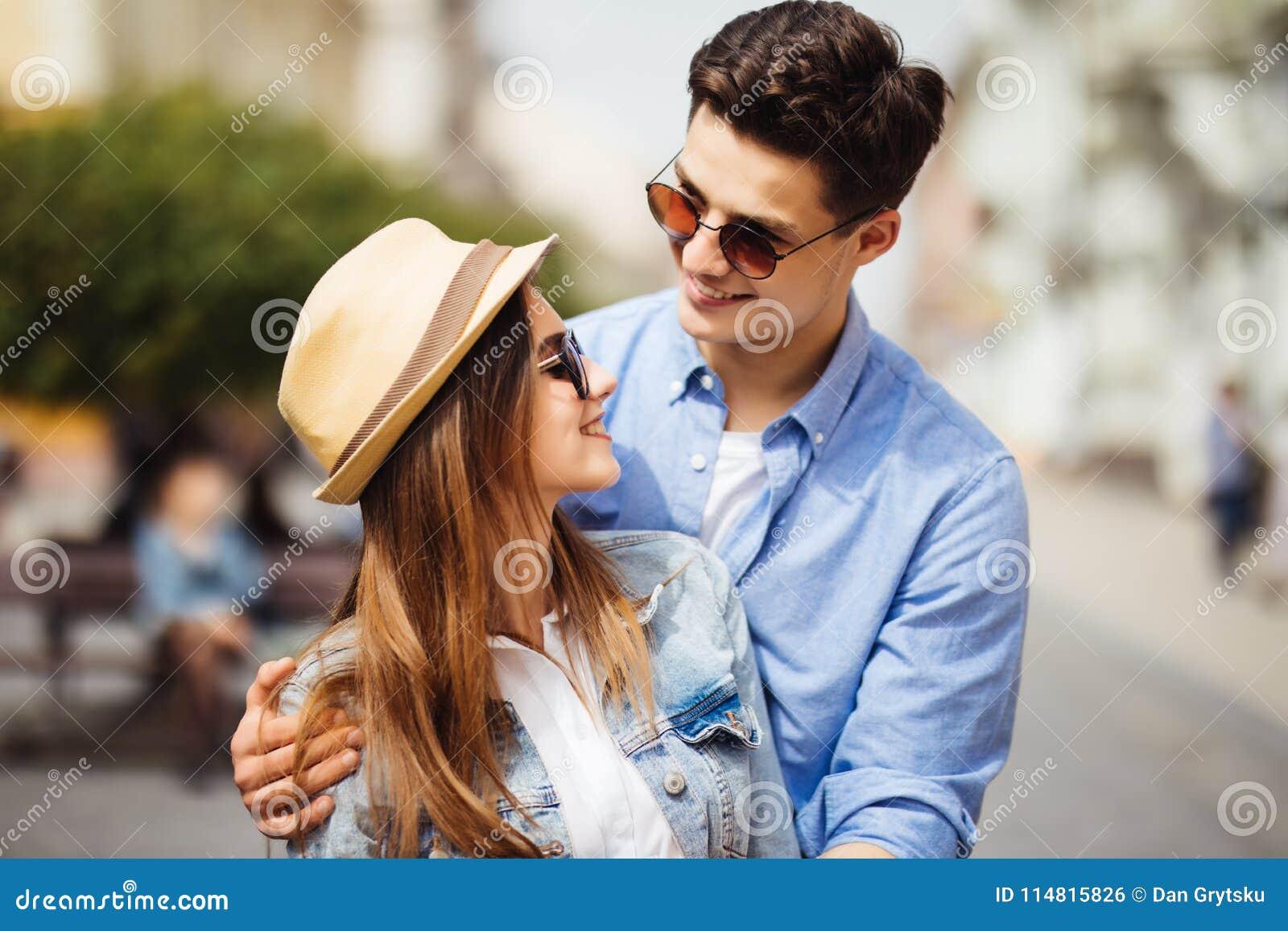 Усмехаясь пары в влюбленности outdoors Молодые счастливые пары обнимая на улице города