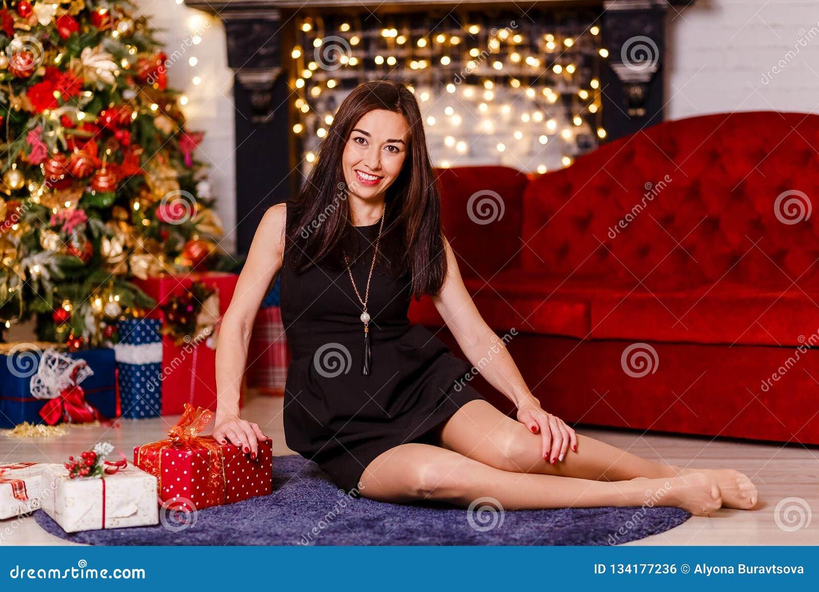 Усмехаясь платье женщины брюнета вкратце черное сидя на поле