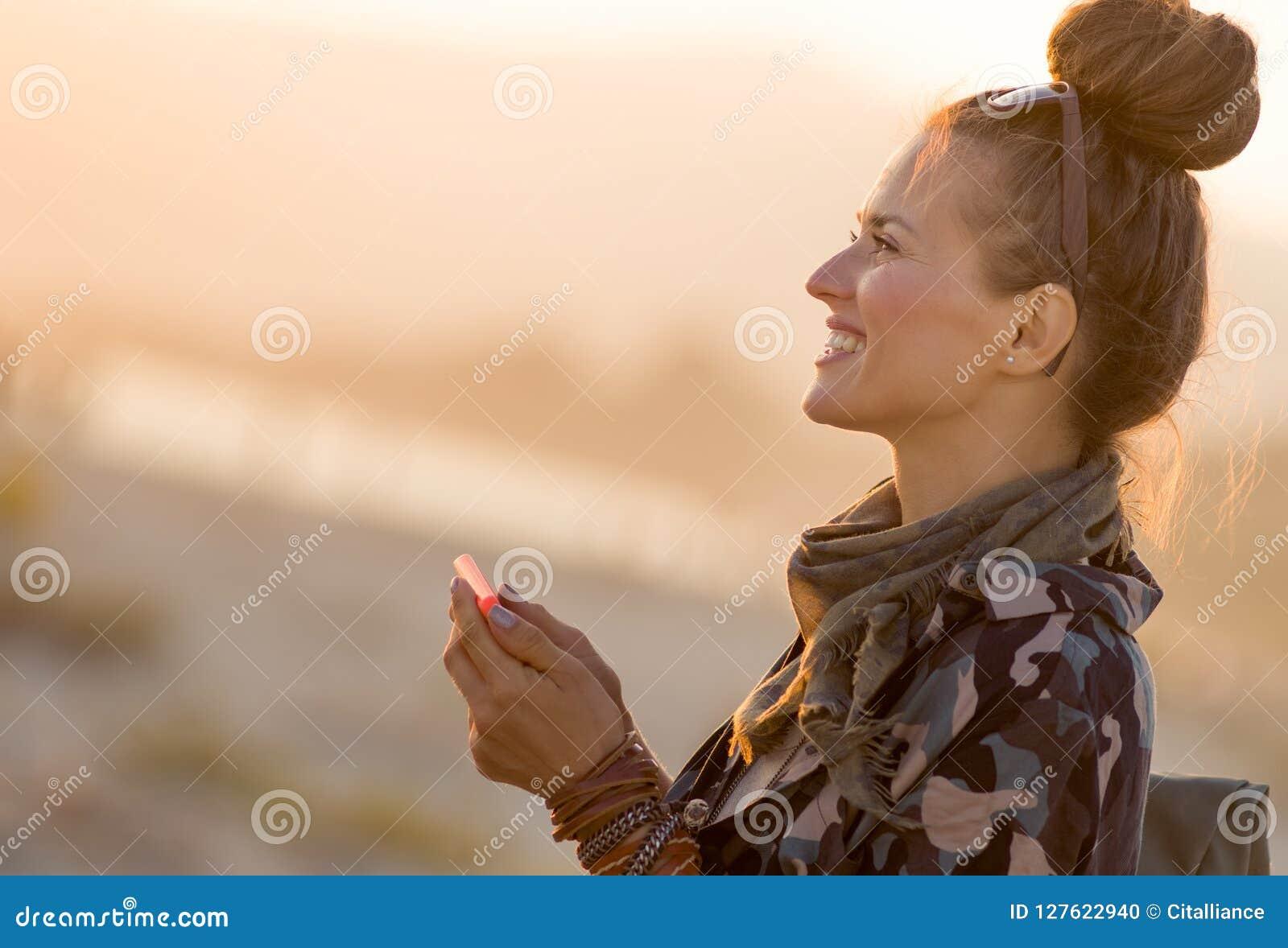 Усмехаясь подходящая туристская женщина с smartphone используя app