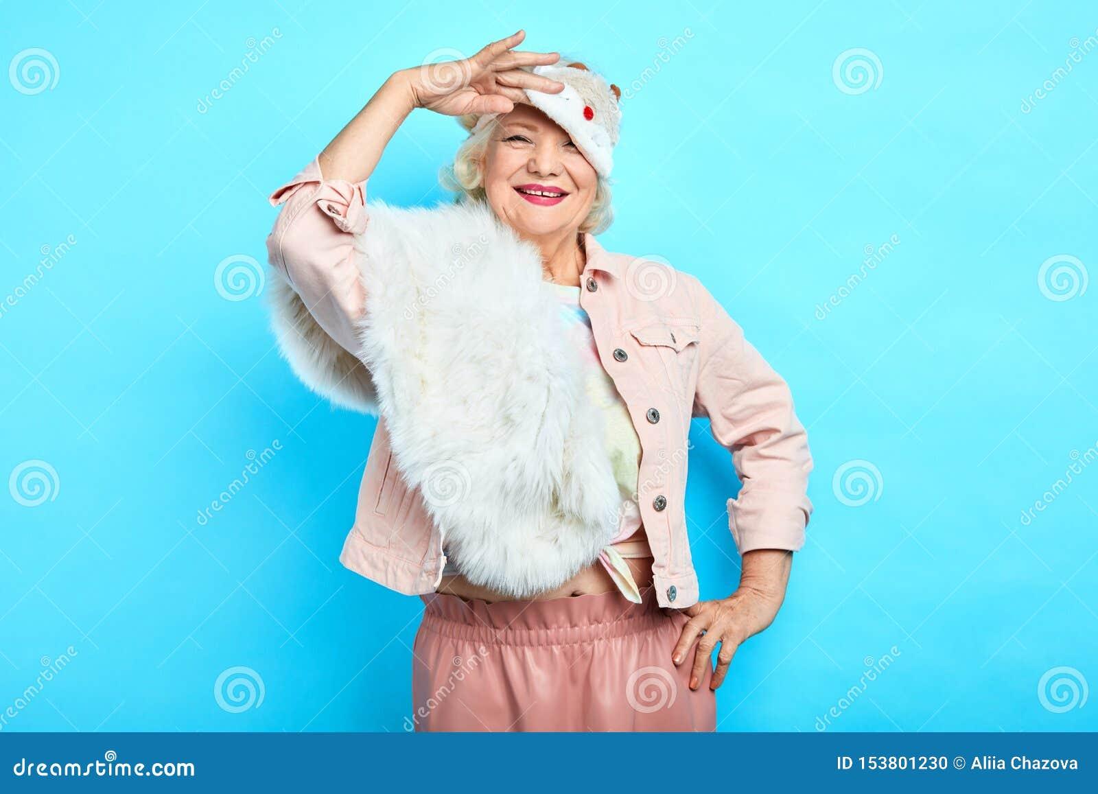 Усмехаясь положительная женщина моды принимая маску