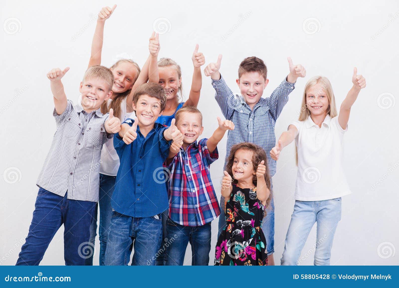 Усмехаясь подростки показывая одобренный знак на белизне