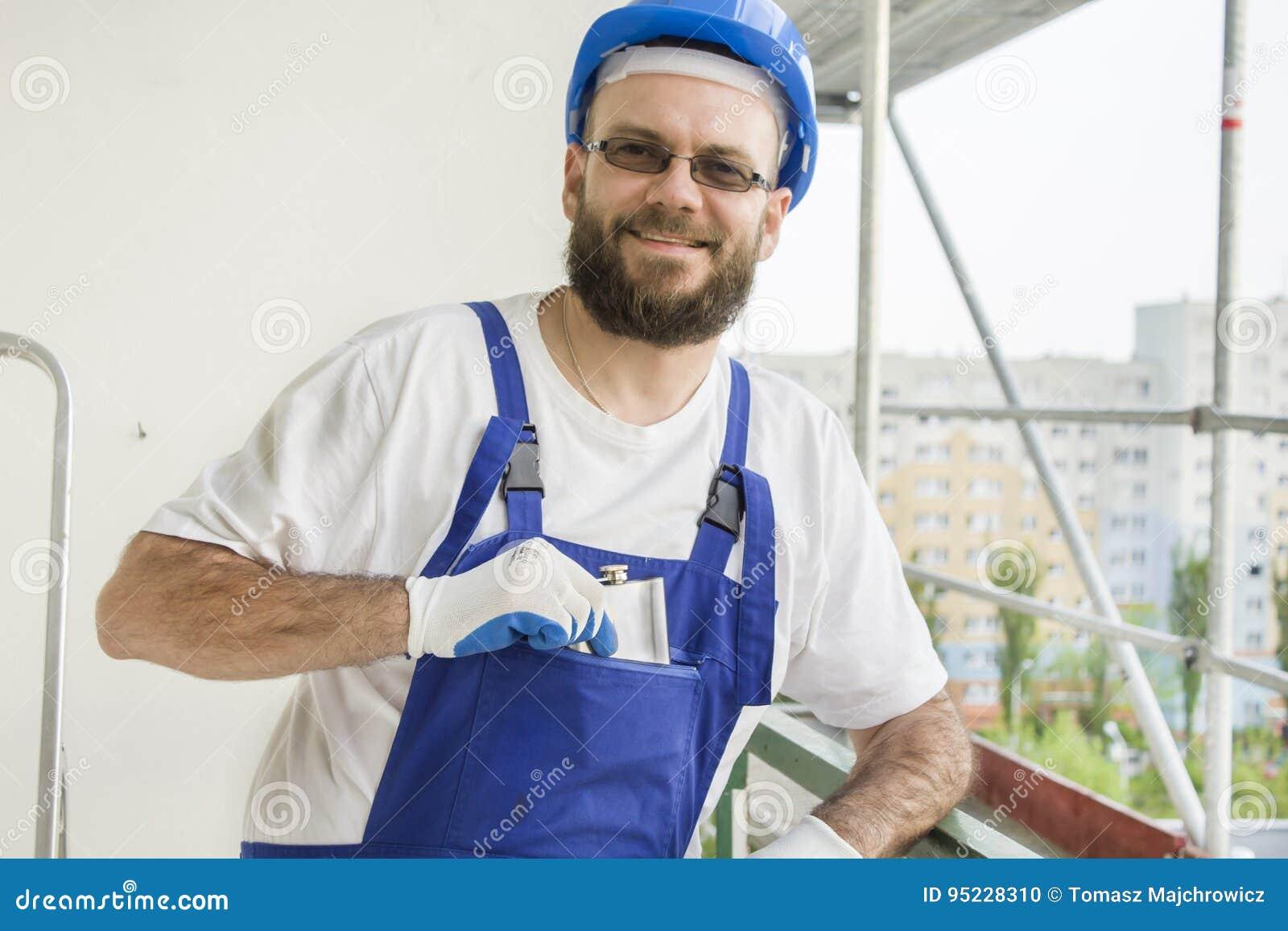 Усмехаясь рабочий-строитель в обмундировании работы, защитных перчатках и шлеме на его голове вытягивает серебряную бедр-склянку