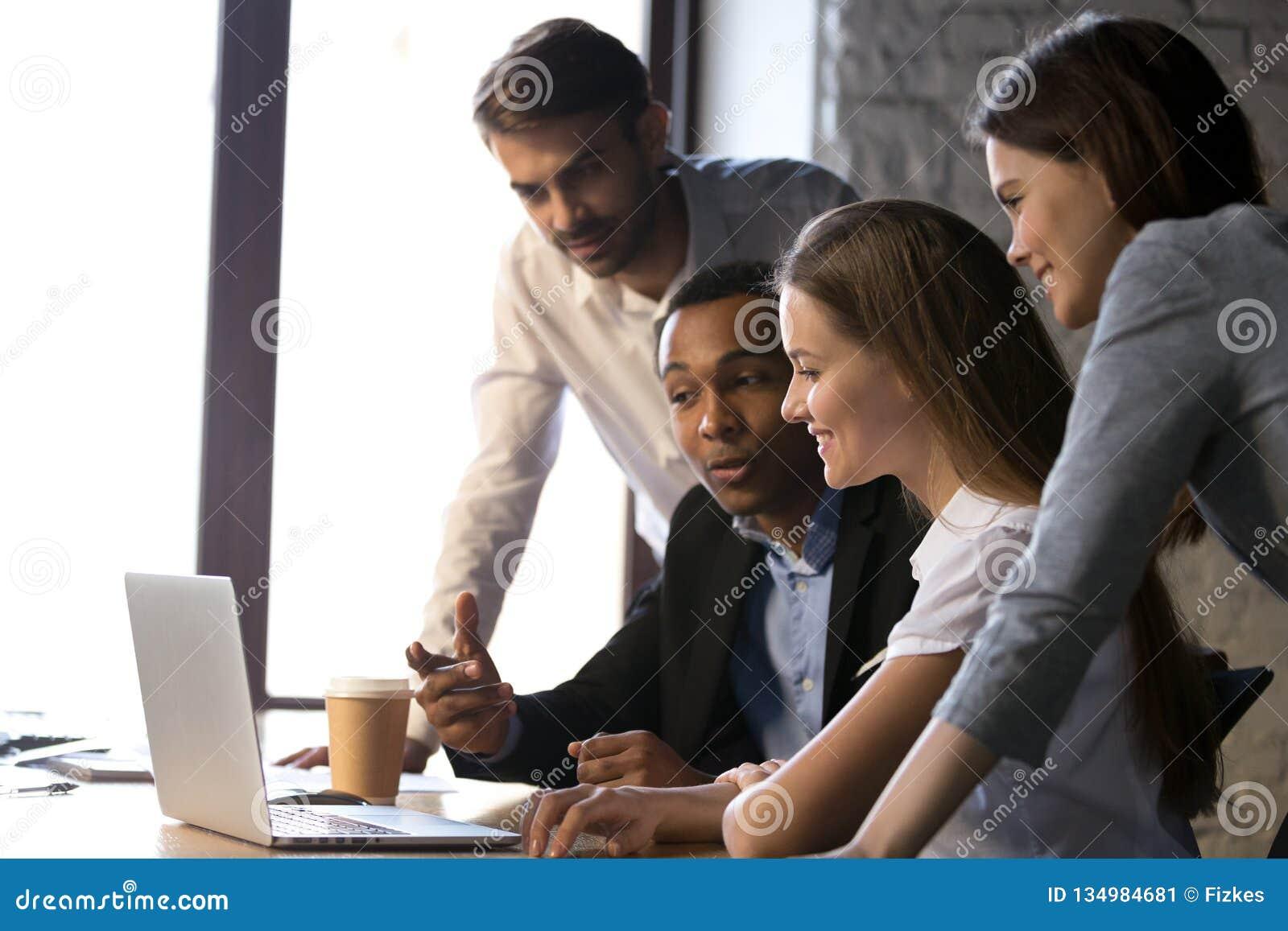 Усмехаясь разнообразная команда используя ноутбук обсуждая онлайн проект на m