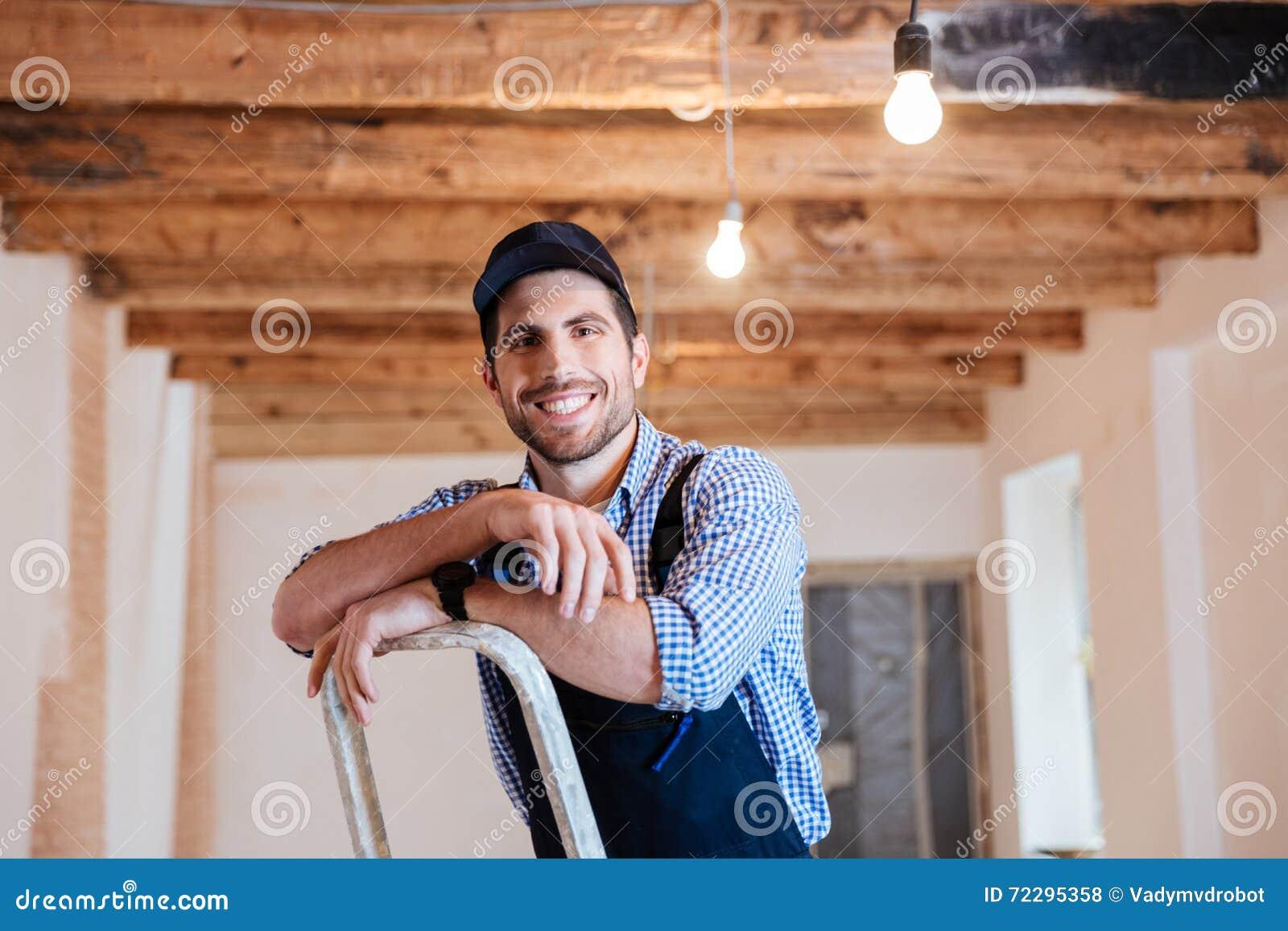 Download Усмехаясь разнорабочий стоя на лестнице Стоковое Фото - изображение насчитывающей выдвинуло, контрактор: 72295358