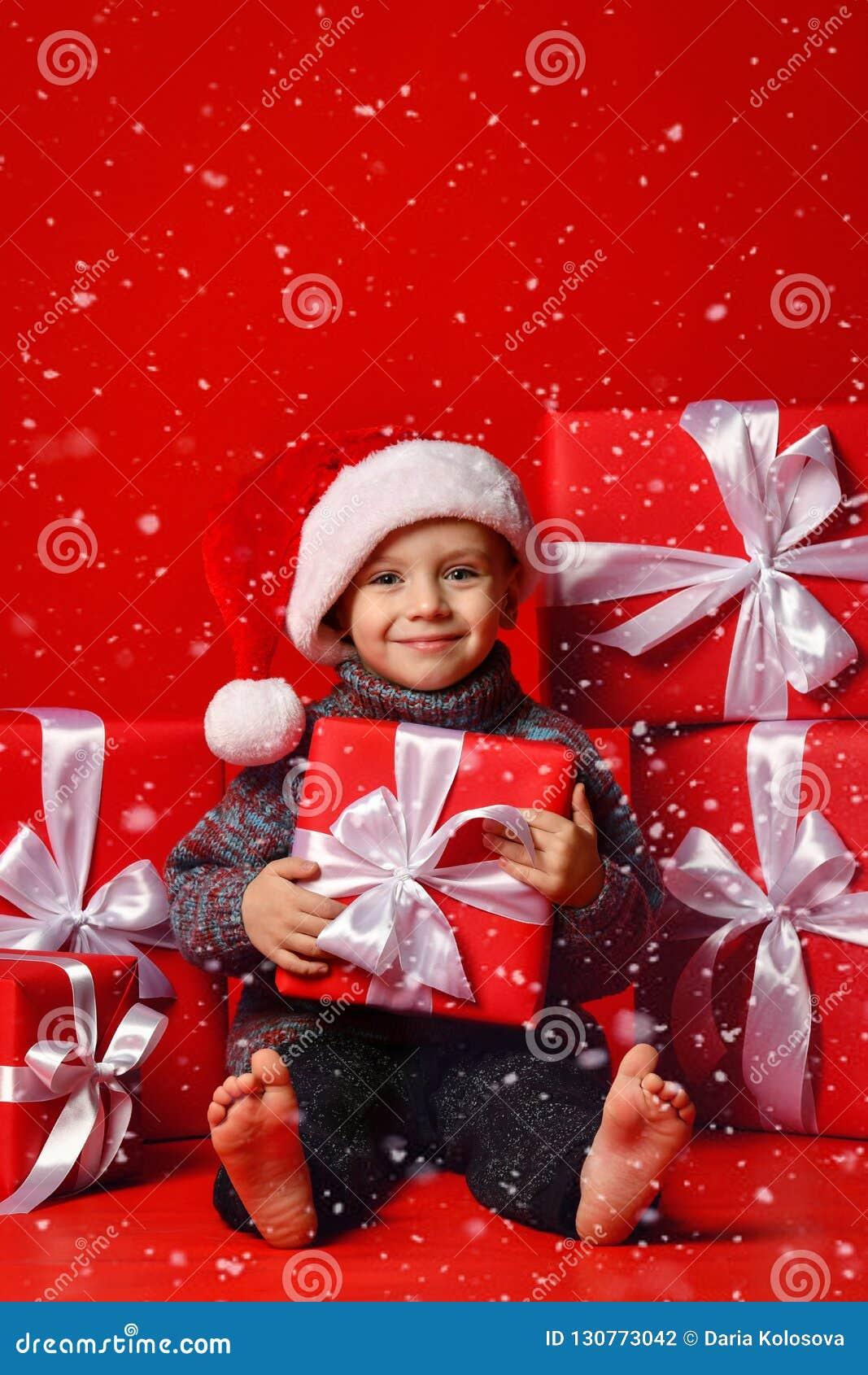 Усмехаясь смешной ребенок в шляпе Санты красной держа подарок рождества в руке Принципиальная схема рождества