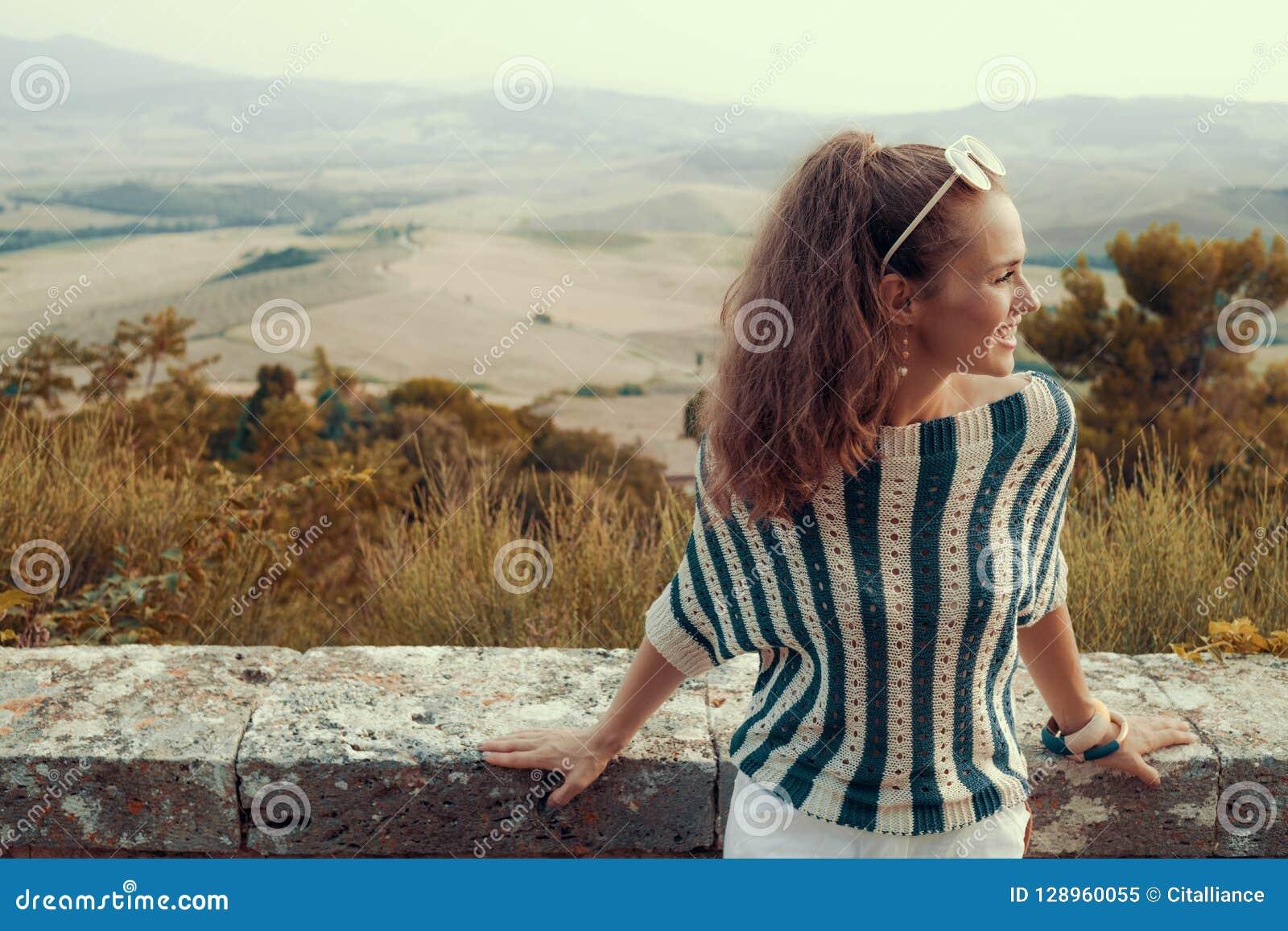 Усмехаясь современная туристская женщина смотря в расстояние