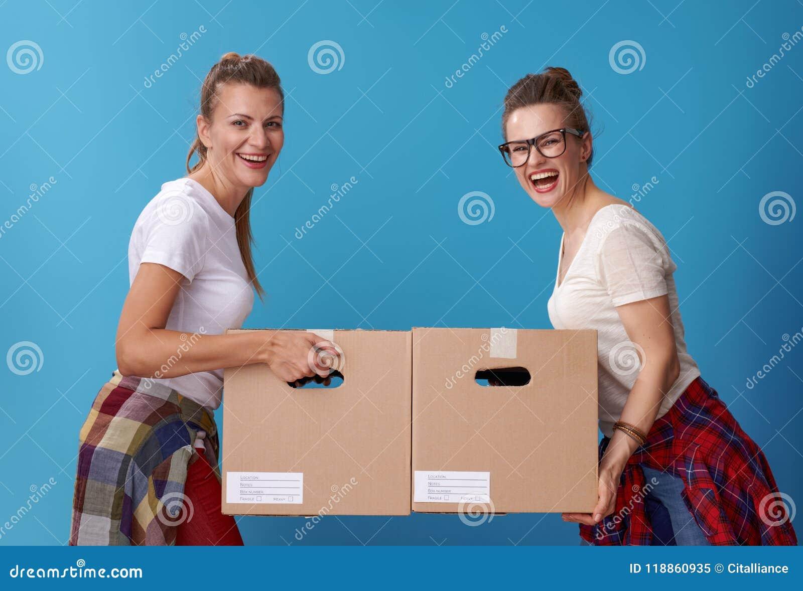 Усмехаясь современные женские соквартиранты с картонными коробками на сини