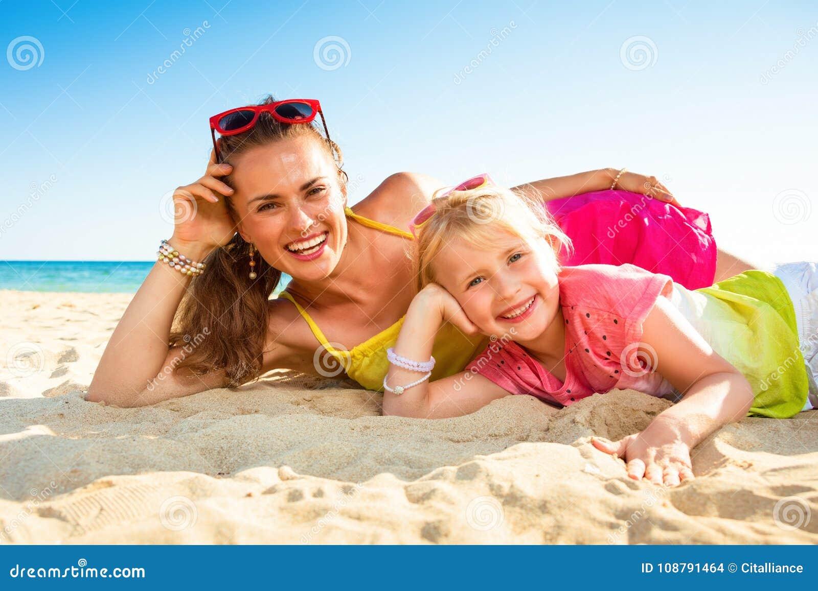 Усмехаясь современные мать и ребенок на класть seashore