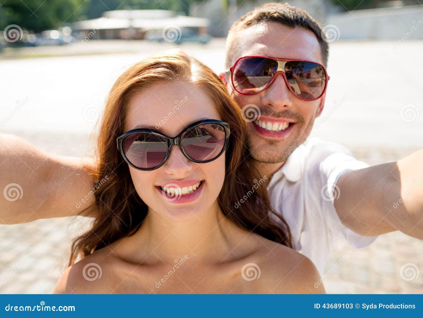 Усмехаясь солнечные очки пар нося делая selfie