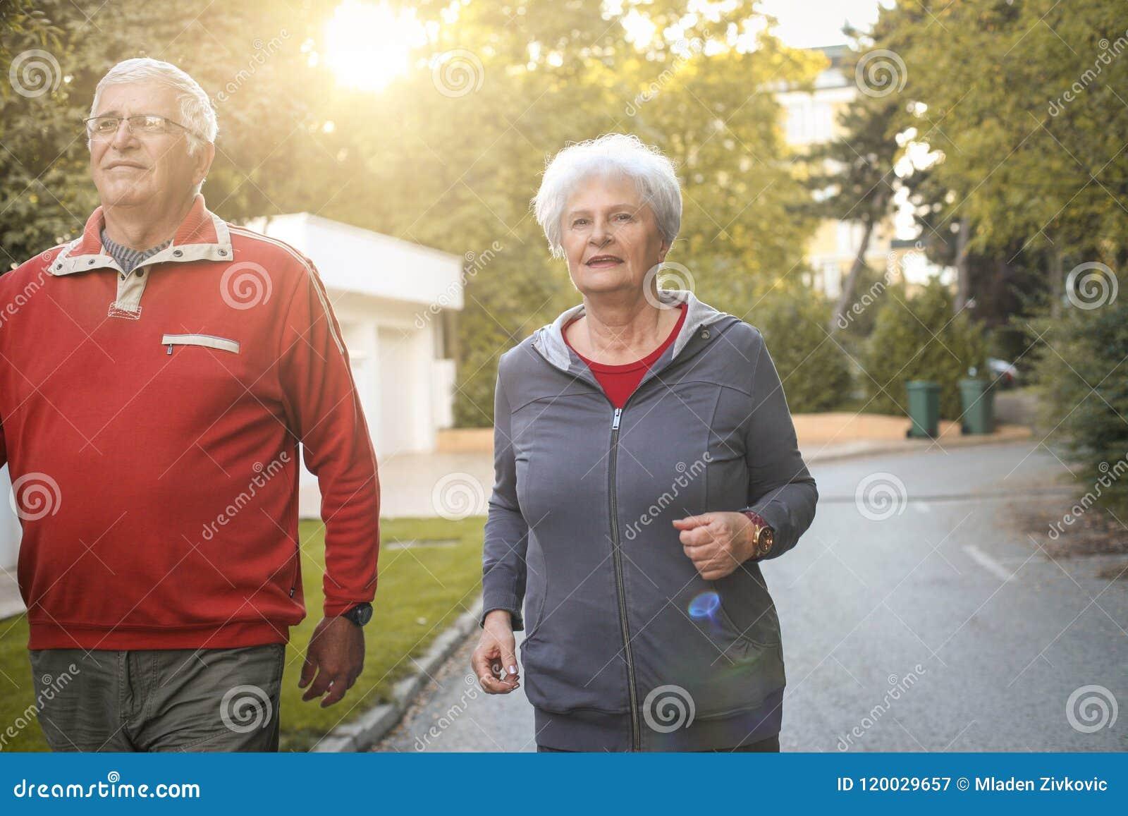 Усмехаясь старшие пары jogging в парке города