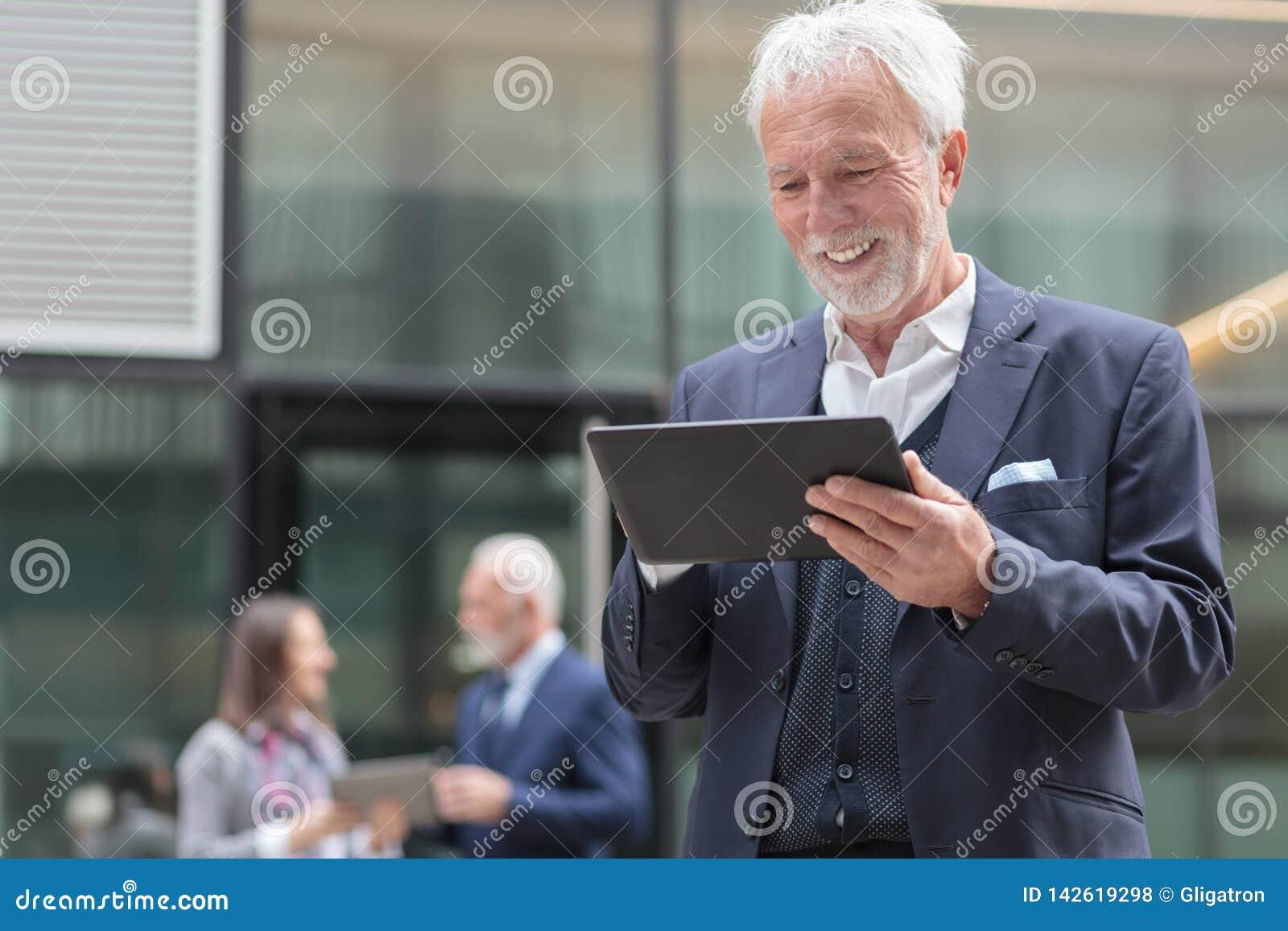 Усмехаясь старший бизнесмен используя планшет, стоя на тротуаре перед офисным зданием