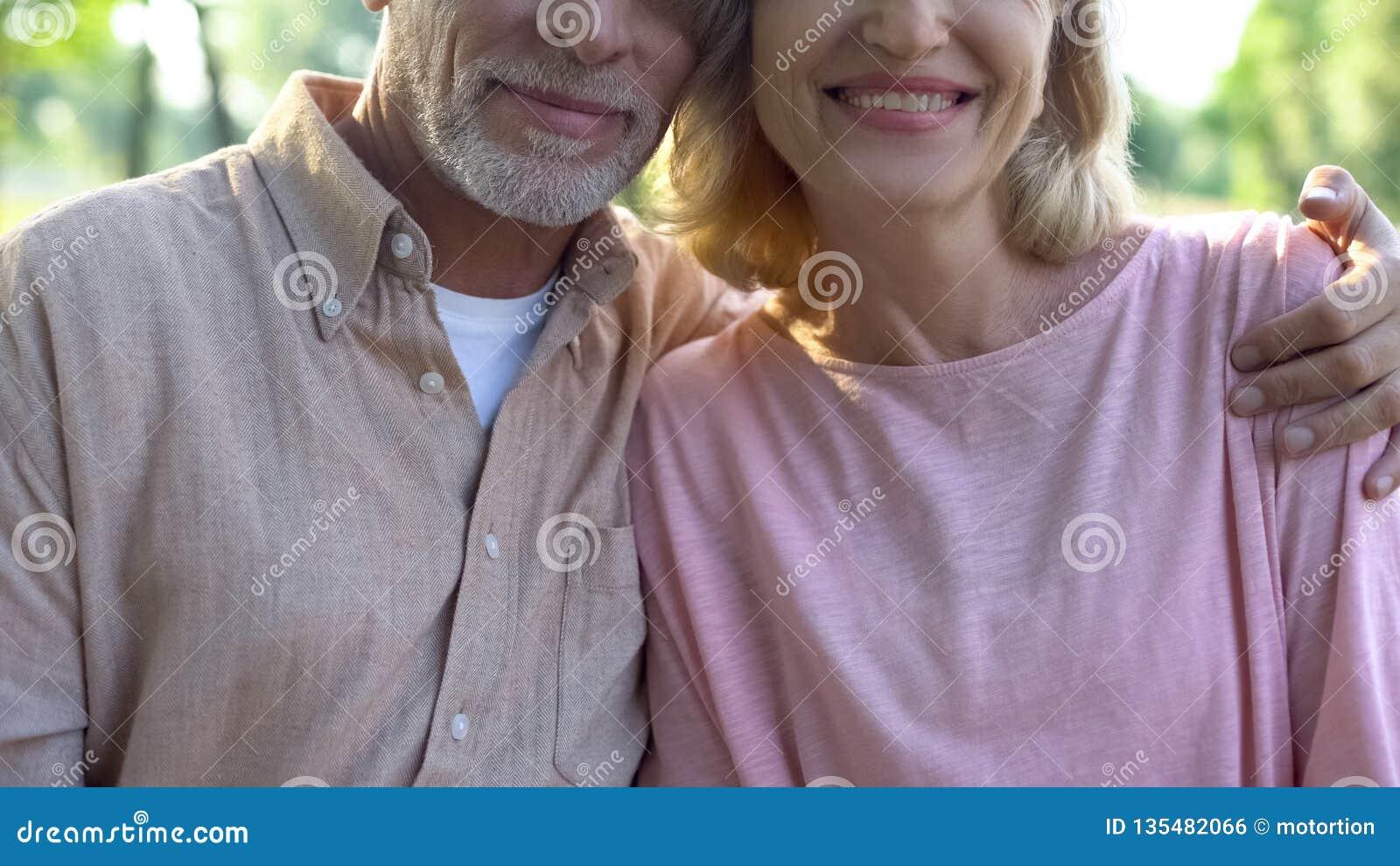 Усмехаясь старый обнимать пар, представляя для камеры, счастье благополучия, привязанность
