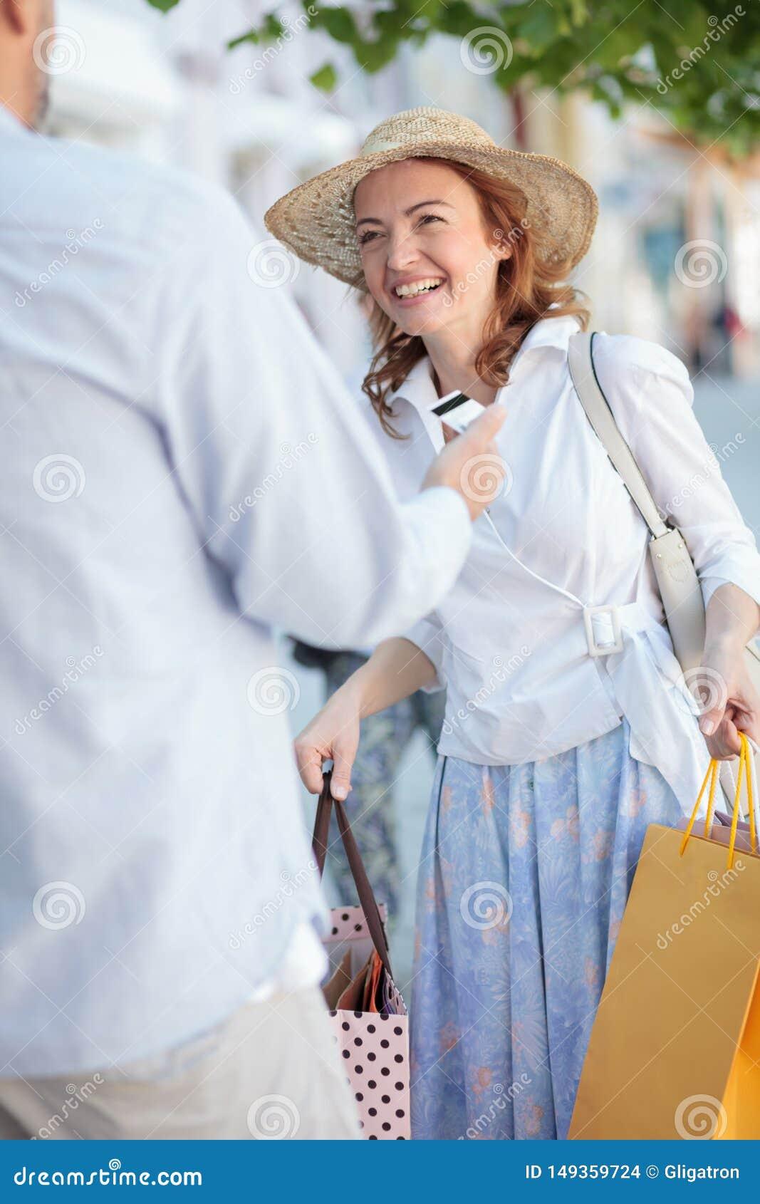 Усмехаясь счастливая зрелая женщина нося полные хозяйственные сумки Ее супруг дает ей автомобиль кредита