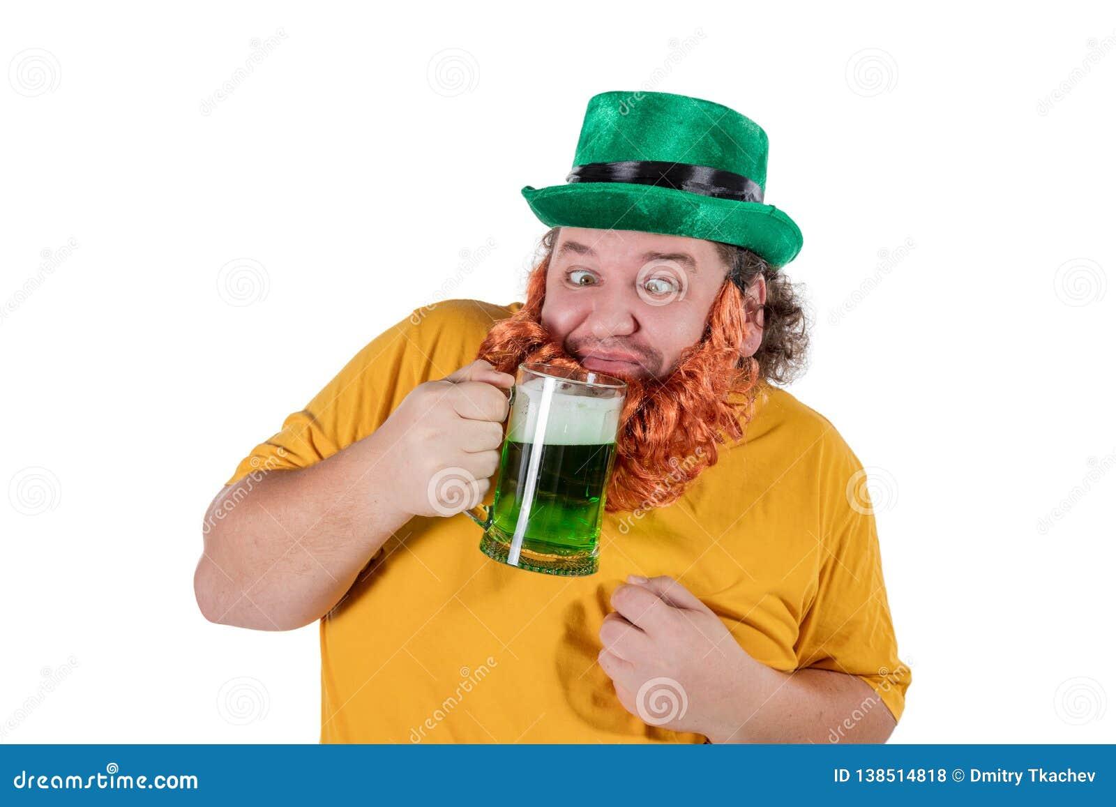 Усмехаясь счастливый жирный человек в шляпе лепрекона с зеленым пивом на студии Он празднует St. Patrick