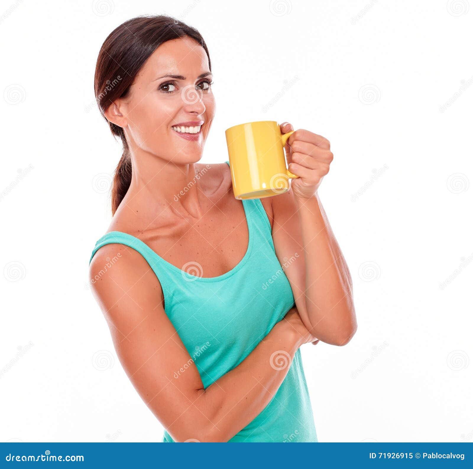 Усмехаясь счастливая женщина брюнет с кружкой кофе