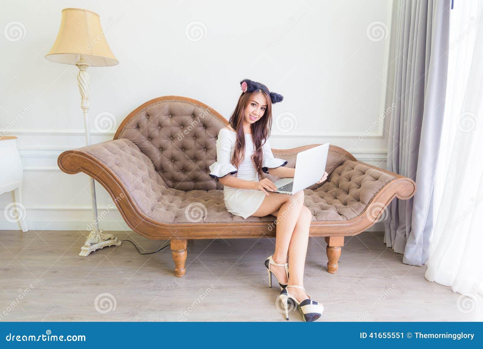 Усмехаясь счастливая женщина сидя на винтажной софе и использовании компьтер-книжки