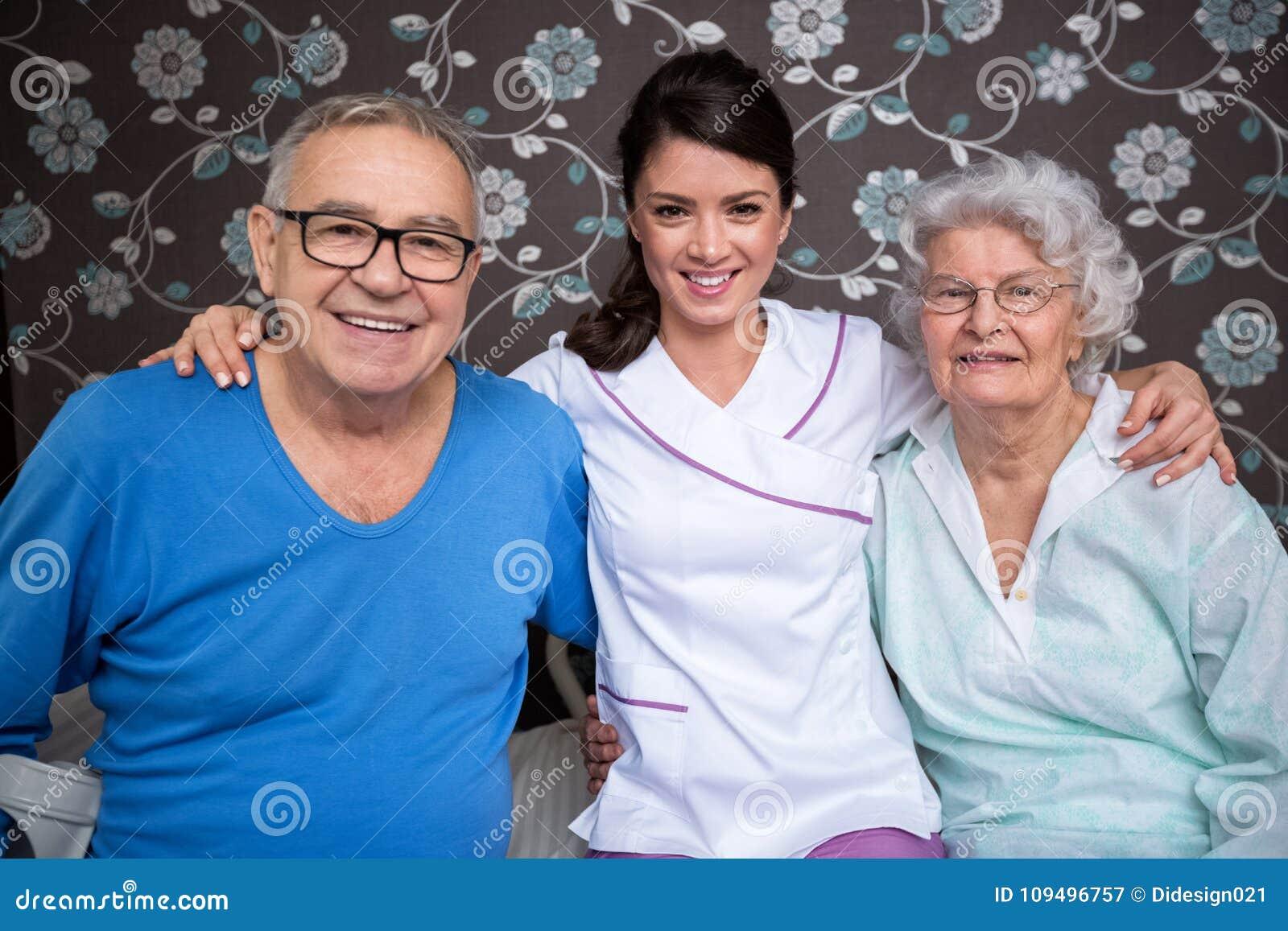 Усмехаясь удовлетворенное престарелое с медсестрой