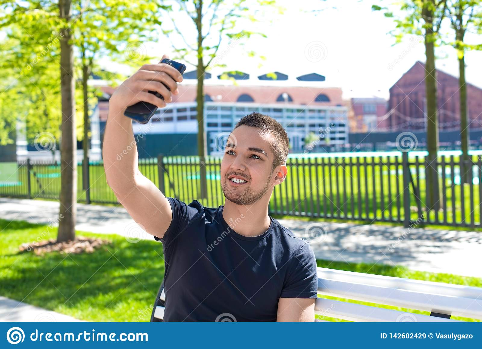 Усмехаясь человек имея онлайн видео- звонок на смартфоне во время свободного времени outdoors