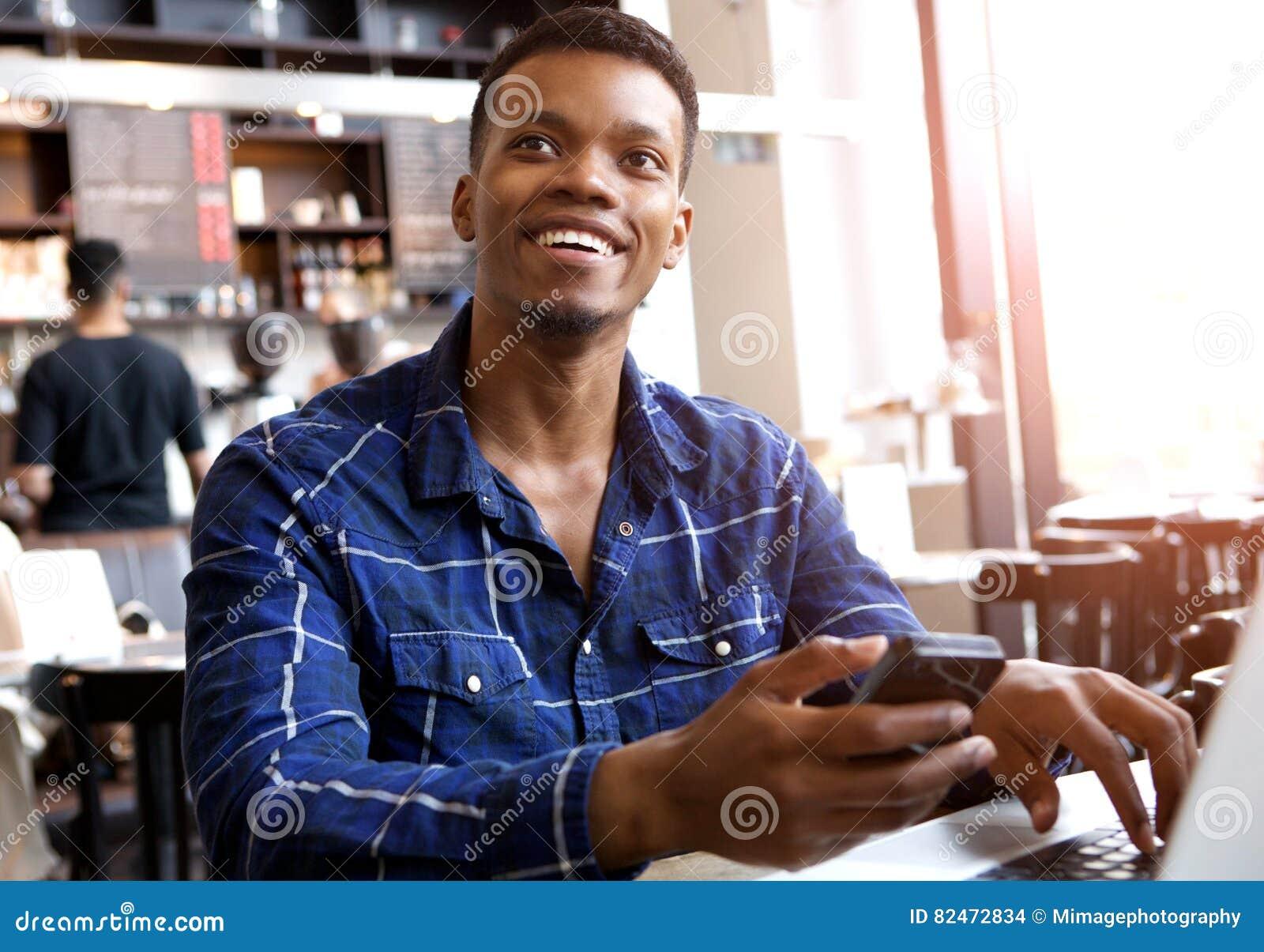 Усмехаясь человек держа мобильный телефон с компьтер-книжкой в кафе