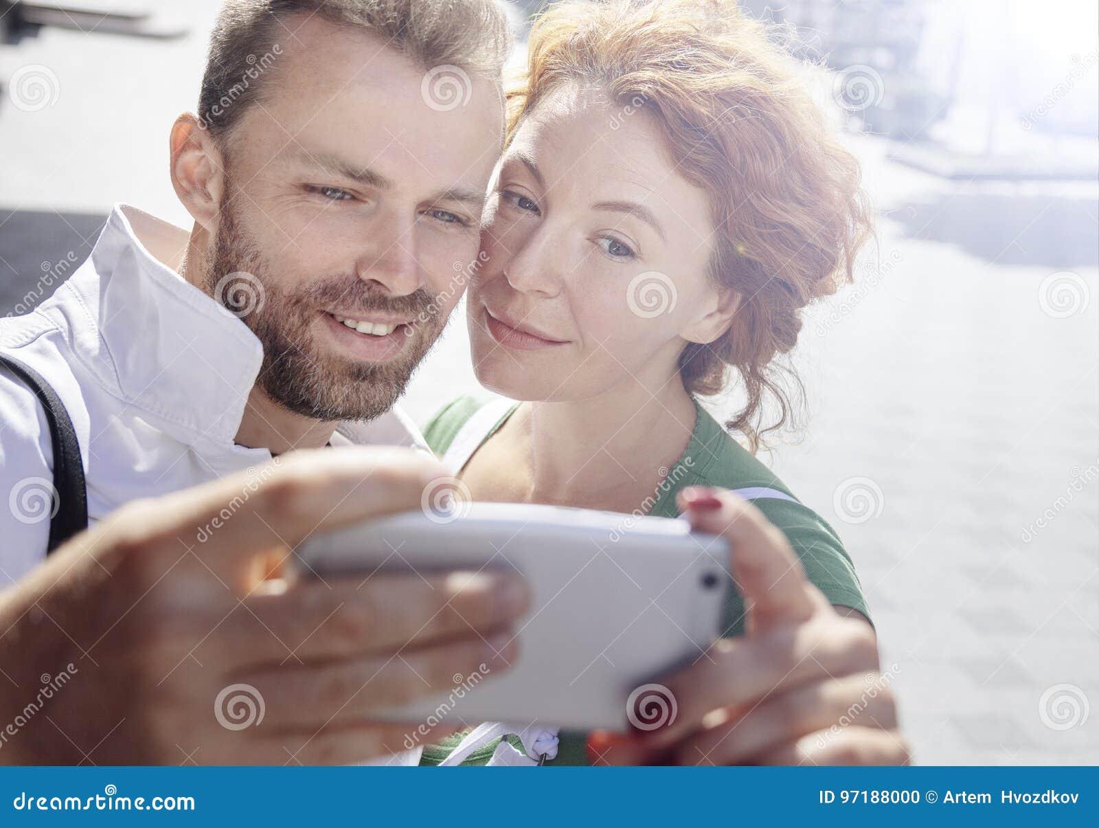 Усмехаясь человек и женщина фотографируя на мобильном телефоне, предпосылке улицы День, внешний
