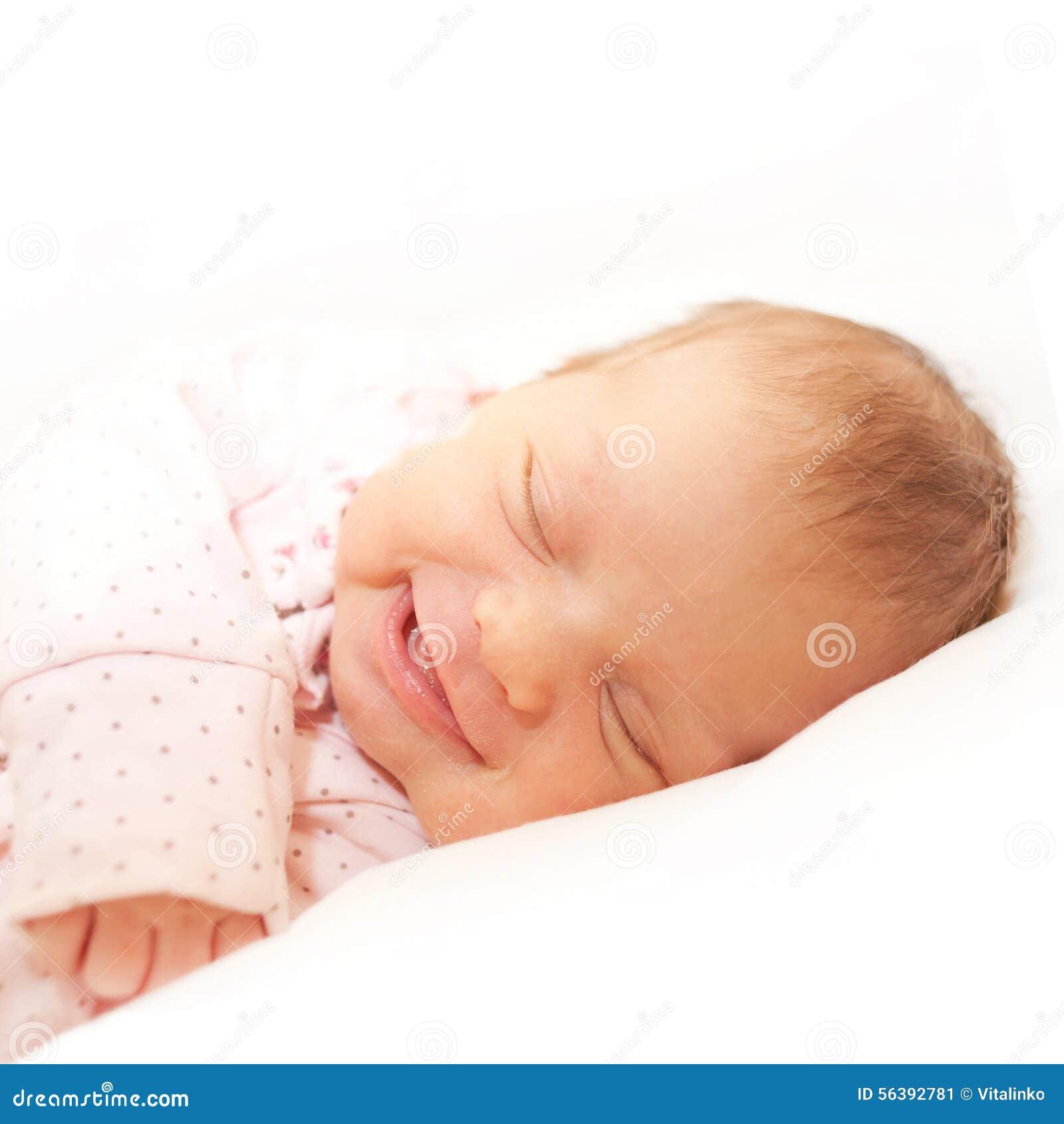 Усмехаясь newborn спать младенца Изолировано на белизне