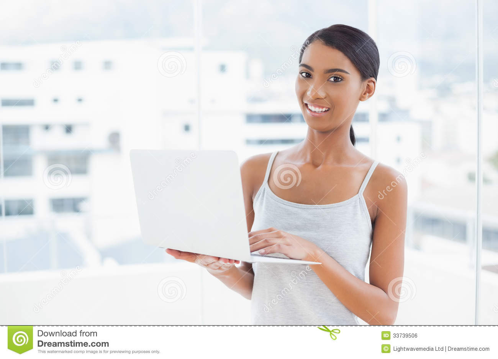 Усмехаясь sporty модель используя ее компьтер-книжку