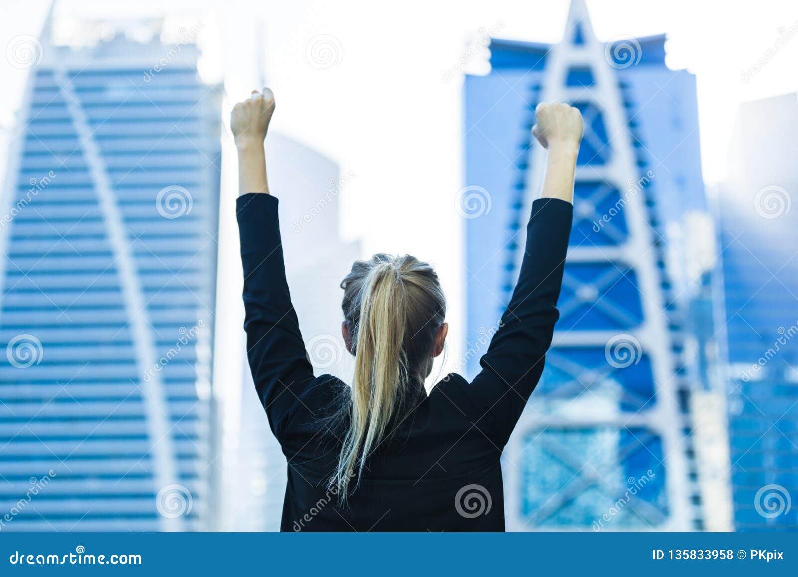 Успех в бизнесе - праздновать коммерсантку обозревая высотные здания центра города