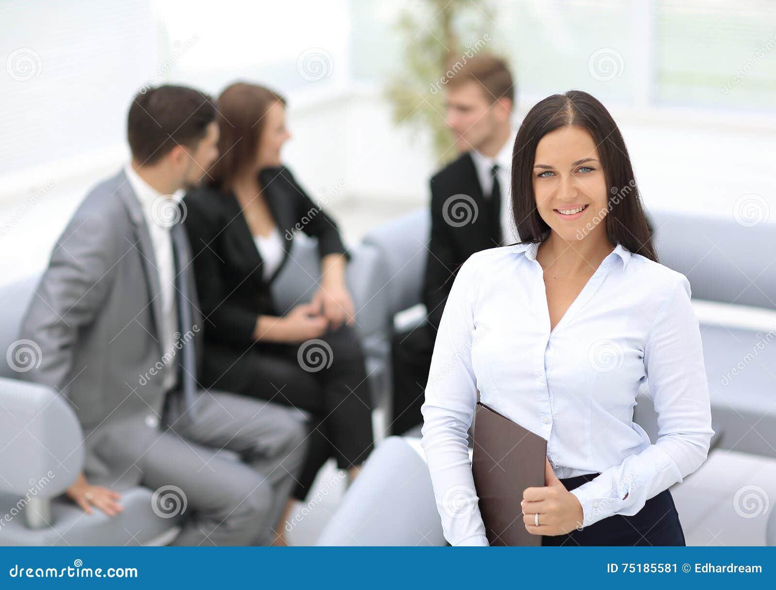 Успешная бизнес-леди стоя с ее штатом в предпосылке