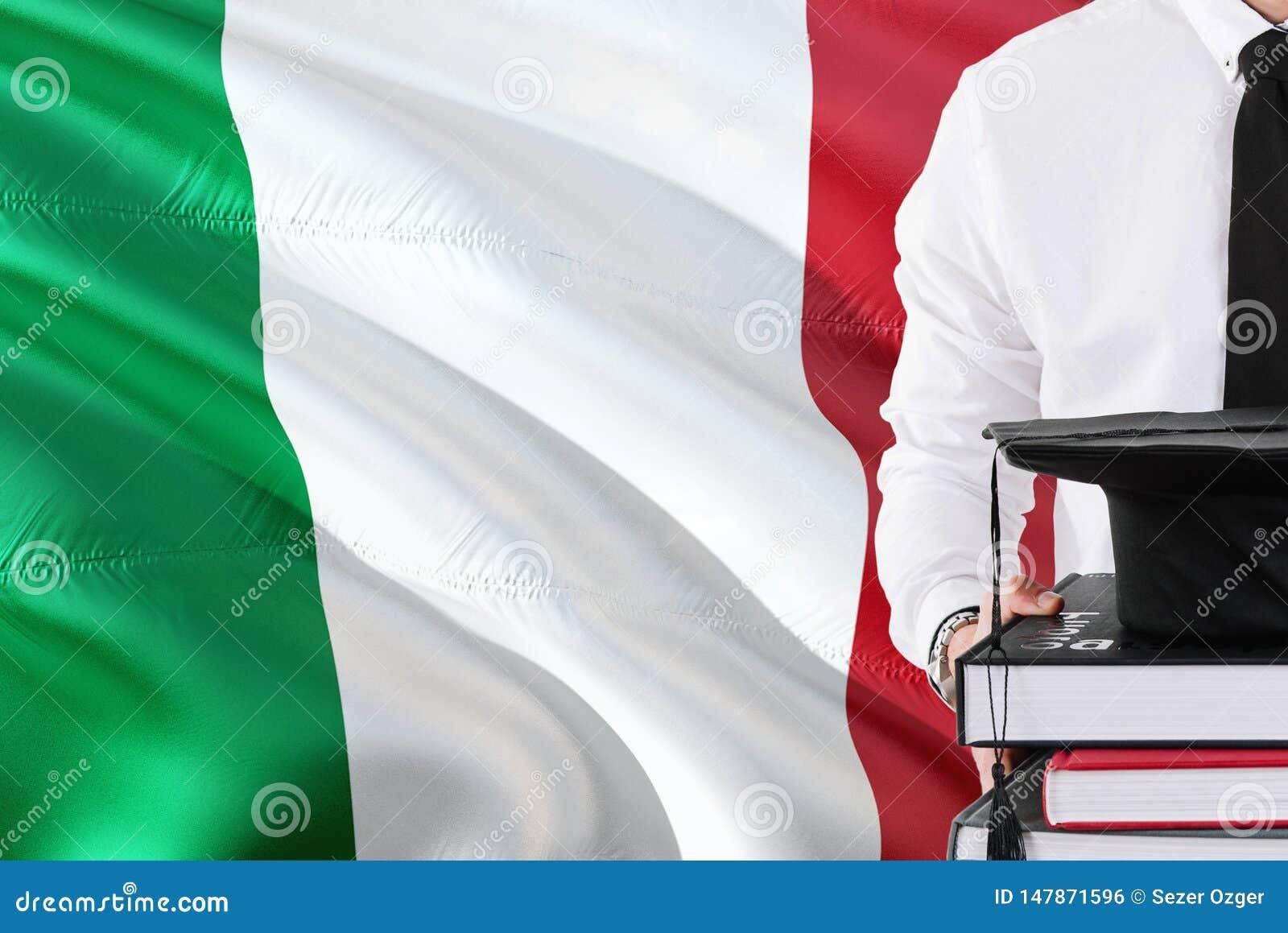 Успешная итальянская концепция образования студента Удержание книг и крышки градации над предпосылкой флага Италии