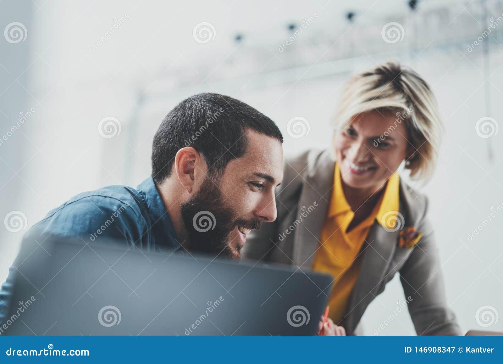 Успешная команда дела на работе Группа в составе молодые бизнесмены работая с ноутбуком и связывая совместно внутри