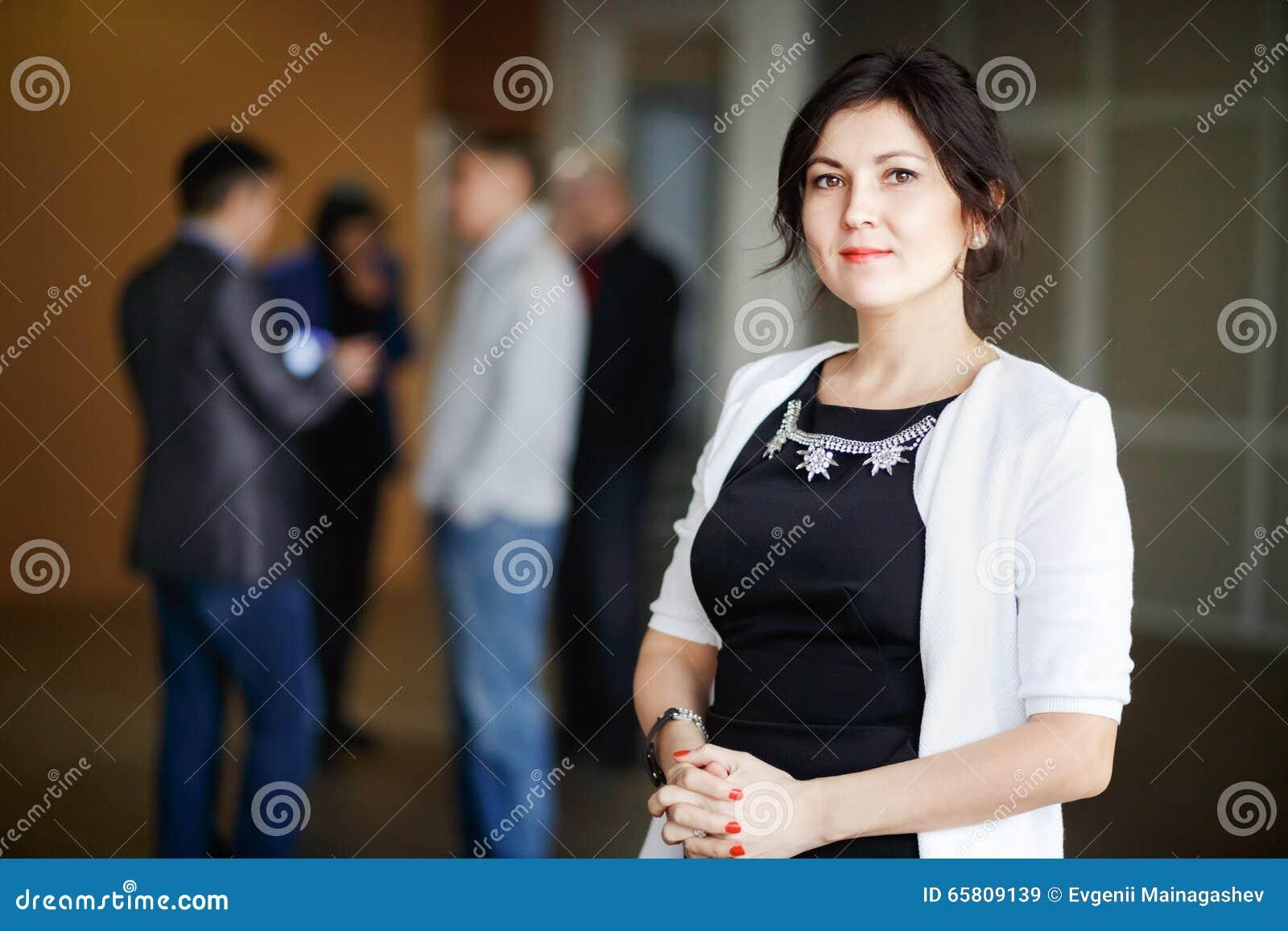 Успешное привлекательное брюнет босса бизнес-леди с глазами вида стоит внутреннее офисное здание и приветствующая улыбка