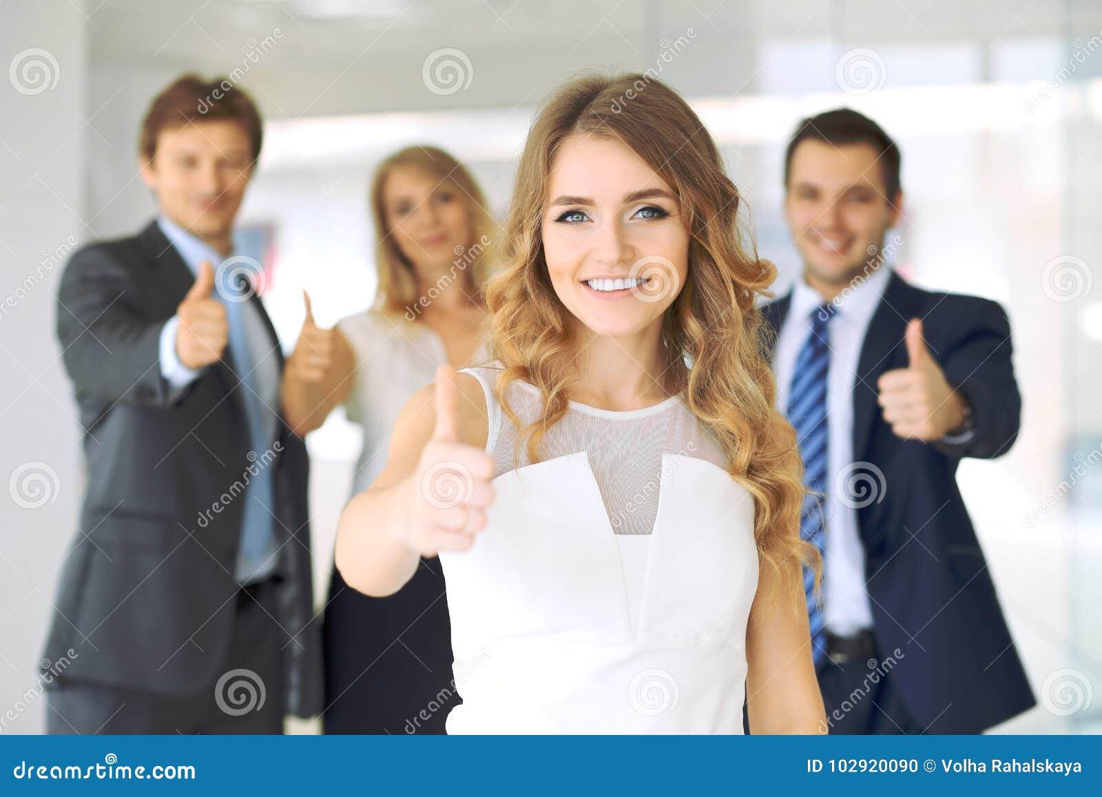 Успешные молодые бизнесмены показывая большие пальцы руки поднимают знак