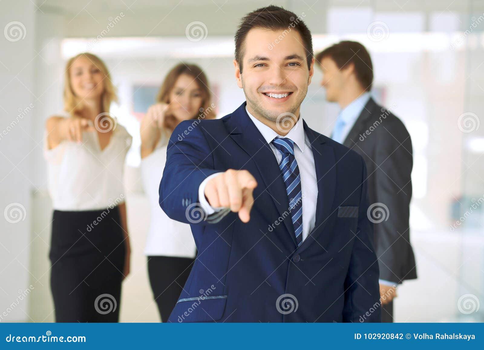 Успешные молодые бизнесмены показывая большие пальцы руки поднимают знак пока стоящ в офисе более interier